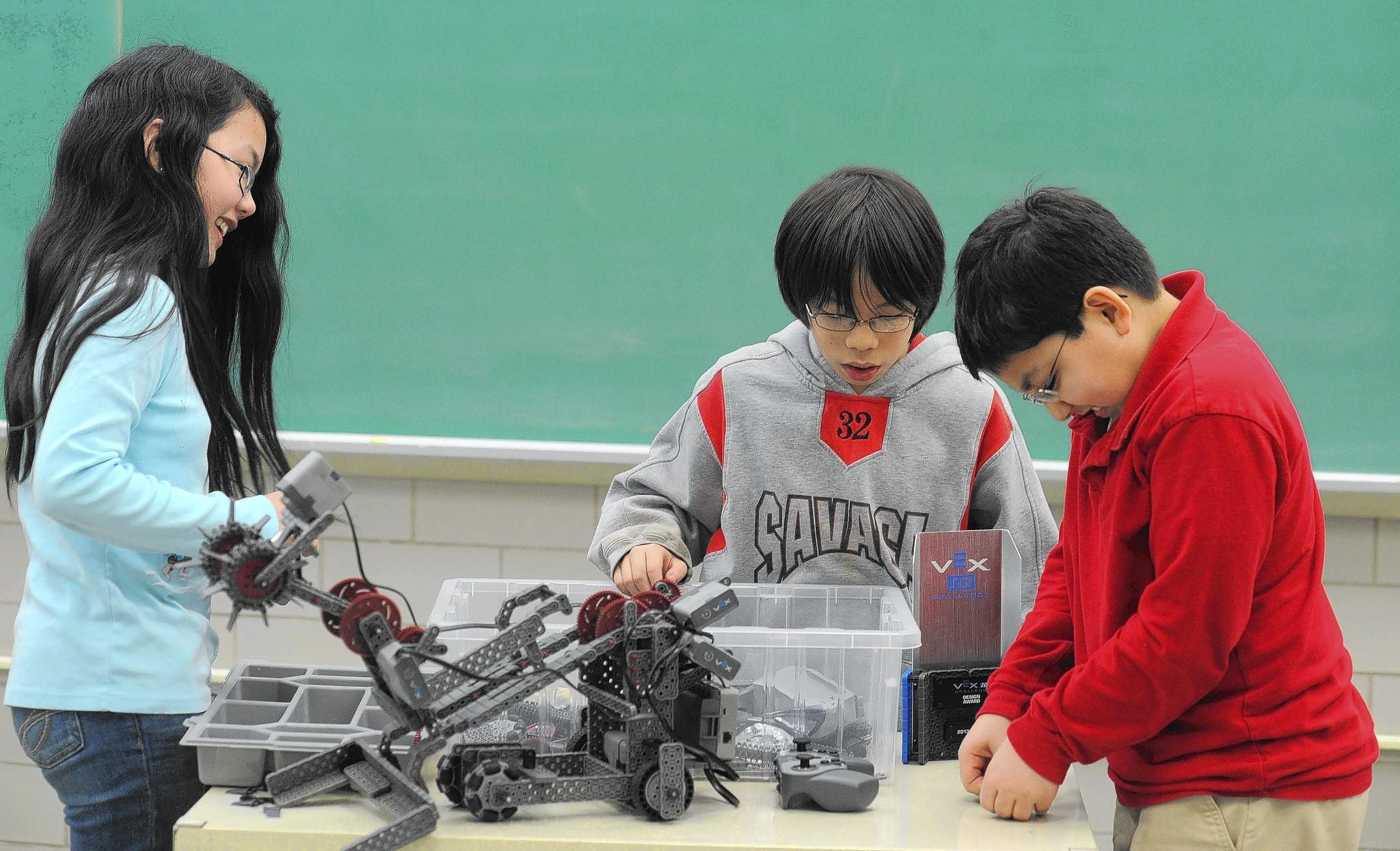 Ridgely Middle School students from left, Cindy Jia, 11, Yuma Sasaki, 11 and Arman Farazdaghi, 12, make adjustments to their team's robot in preparation for the upcoming VEX Robotics Championship in Anaheim, Calif. in April.