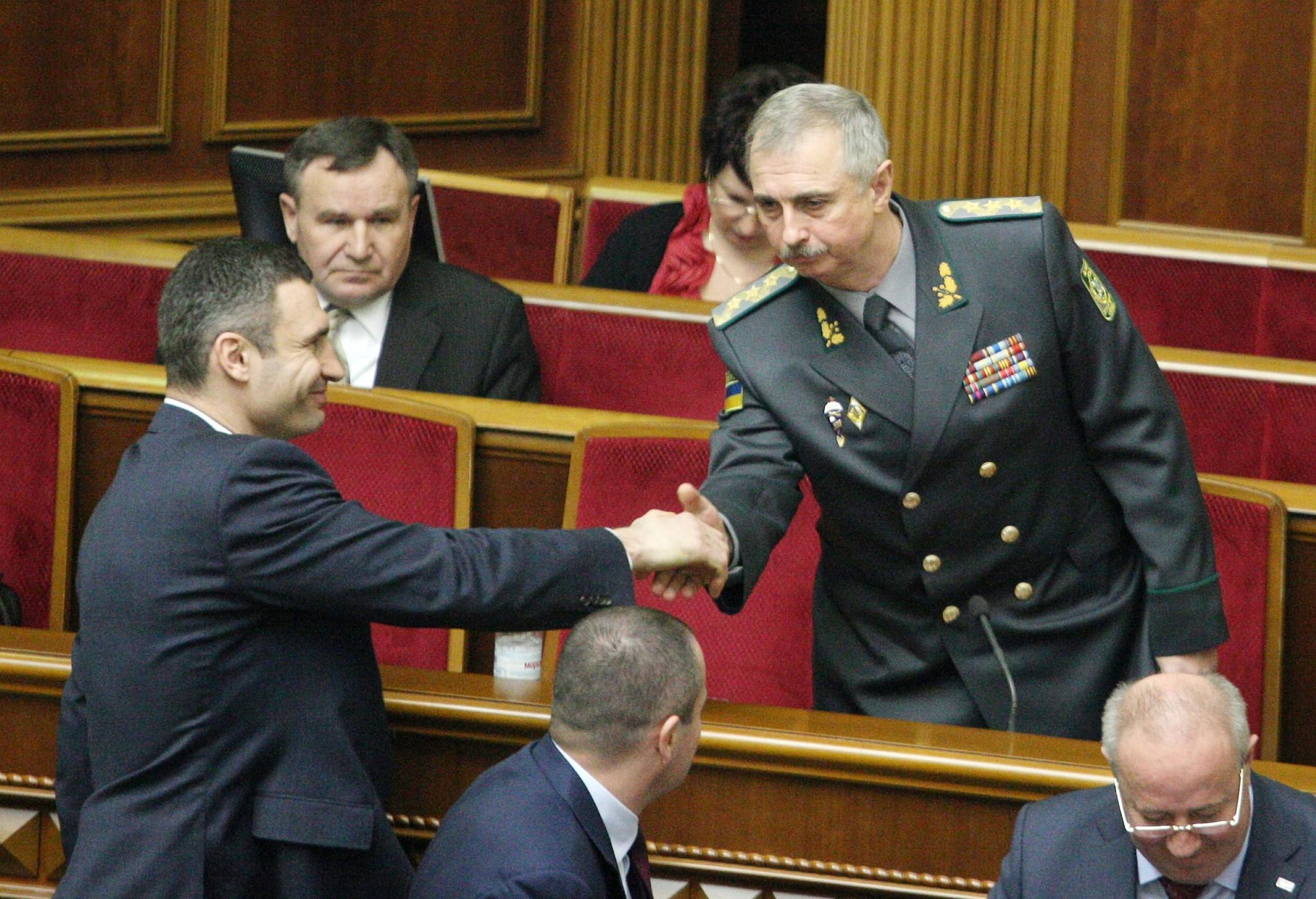 Ukrainian politician and former boxing champion Vitali Klitschko, left, shakes hands with newly appointed acting Defense Minister Mykhailo Koval on Tuesday in Kiev during a session of parliament.