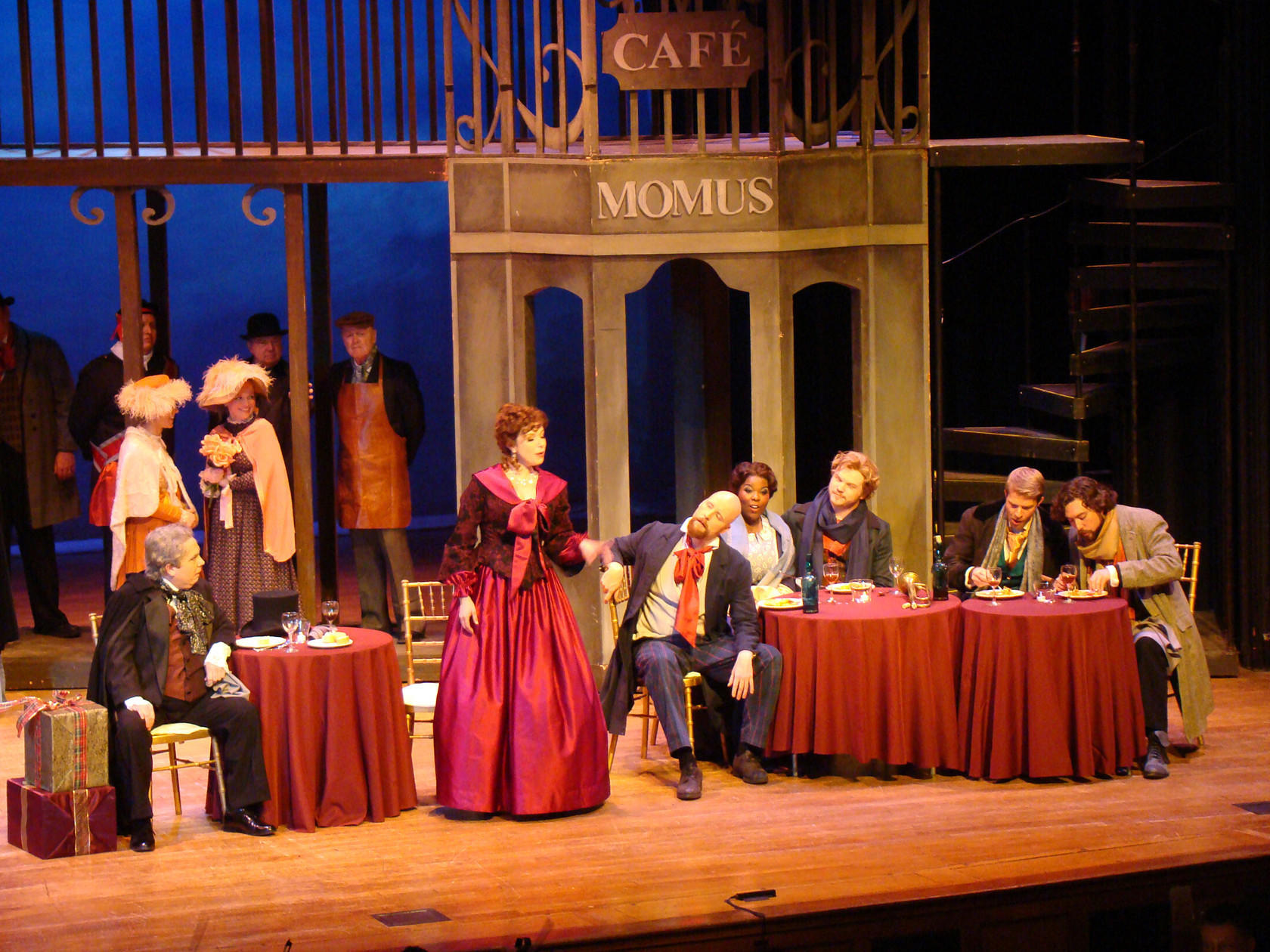 "From far left, Andrew Adelsberger as Alcindoro, Colleen Daly as Musetta, Timothy Mix as Marcello, Michelle Johnson as Mimi, Sean Arnold as Rodolfo, Gregory Gerbrandt as Schaunard and Bradley Smoak as Colline in Annapolis Opera's production of Giacomo Puccini's ""La Boheme."""