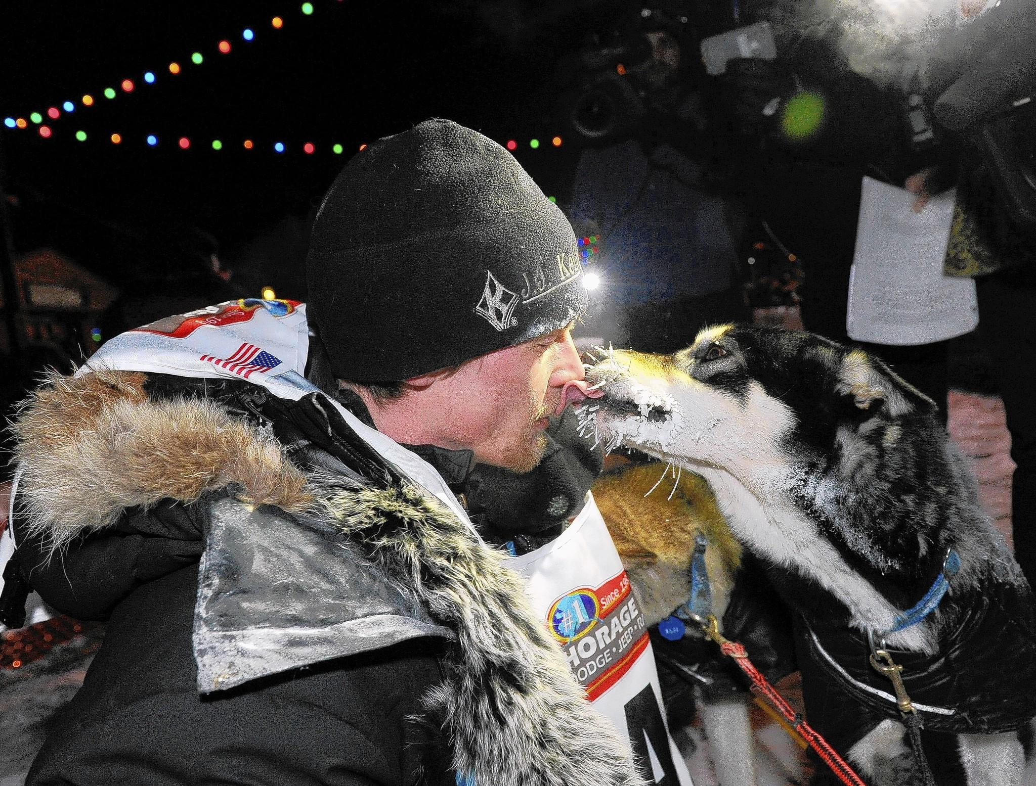 Dallas Seavey gets a kiss from one of his dogs after crossing under the burled arch in Nome, Alaska to win the 2014 Iditarod Trail Sled Dog Race on Tuesday, March 11, 2014.