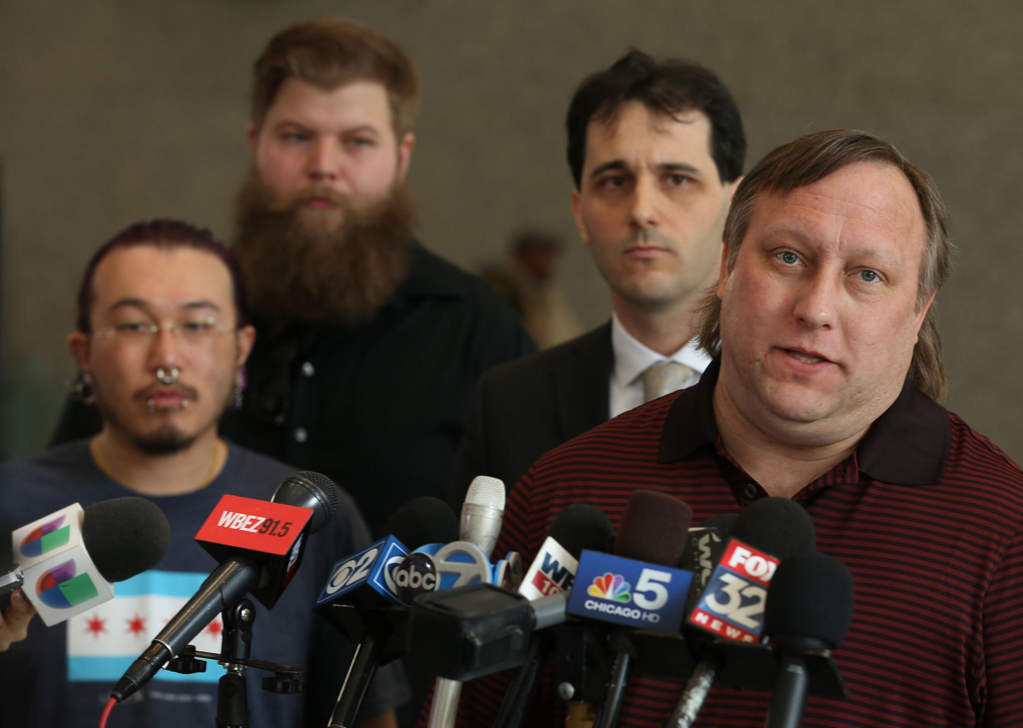 Rideshare drivers Ted Liu, left, Dustin Morby, second from left, attorney Anthony Sanders, second from right, listen to rideshare driver Dan Burgess, right talk about a motion to intervene in the lawsuit that ridershare drivers say threatens their services.