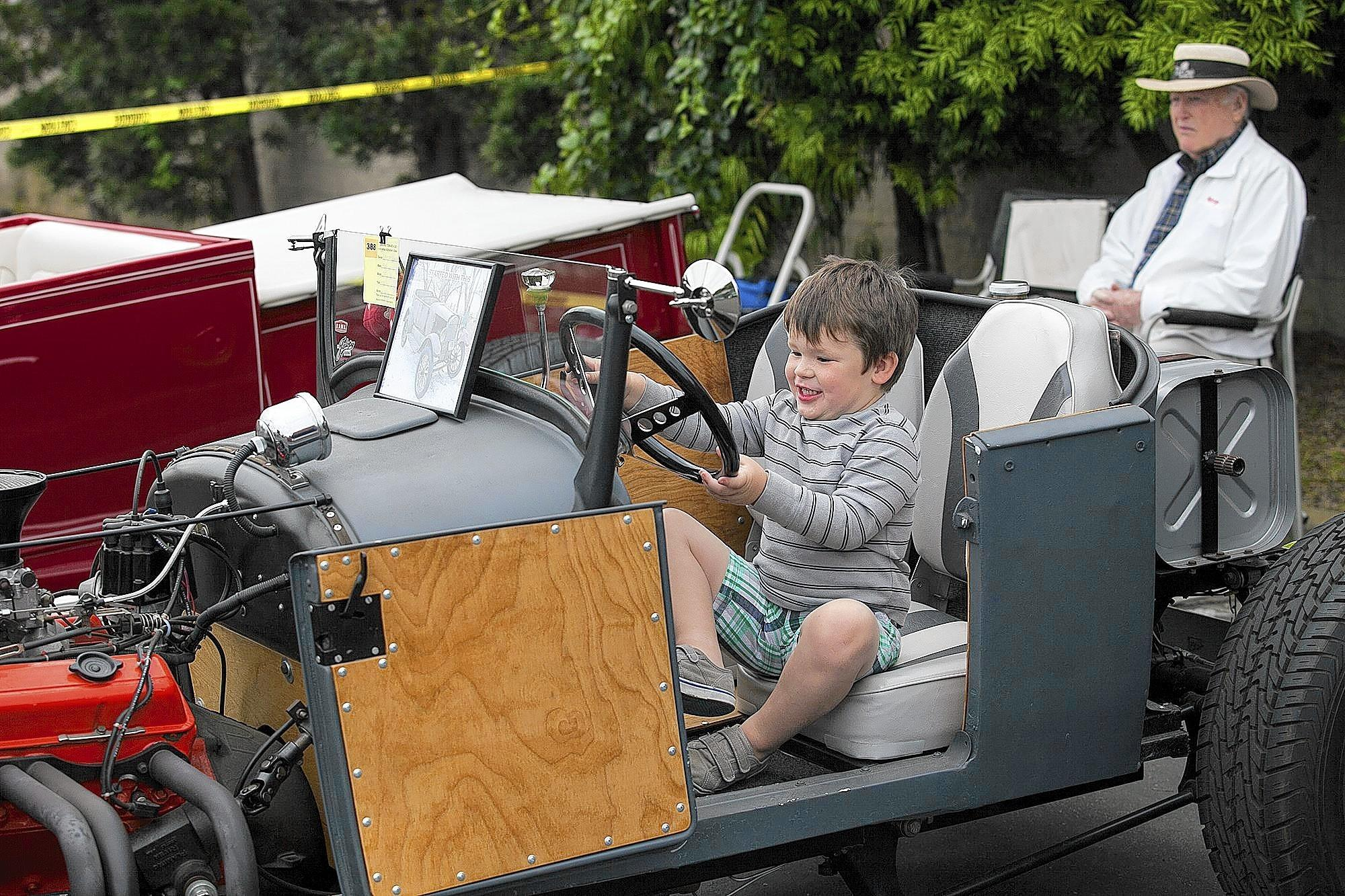 Colin Hunnel, 3, sits behind the wheel of a 1926 Ford Model T during the Sixth Annual Driving a Cure For Alzheimer's Disease Classic Car Show in Huntington Beach on Saturday.
