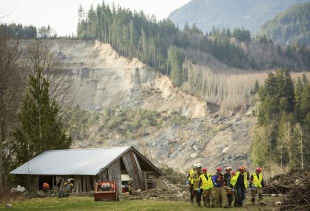 A body is carried out of a home destroyed by the mudslide.