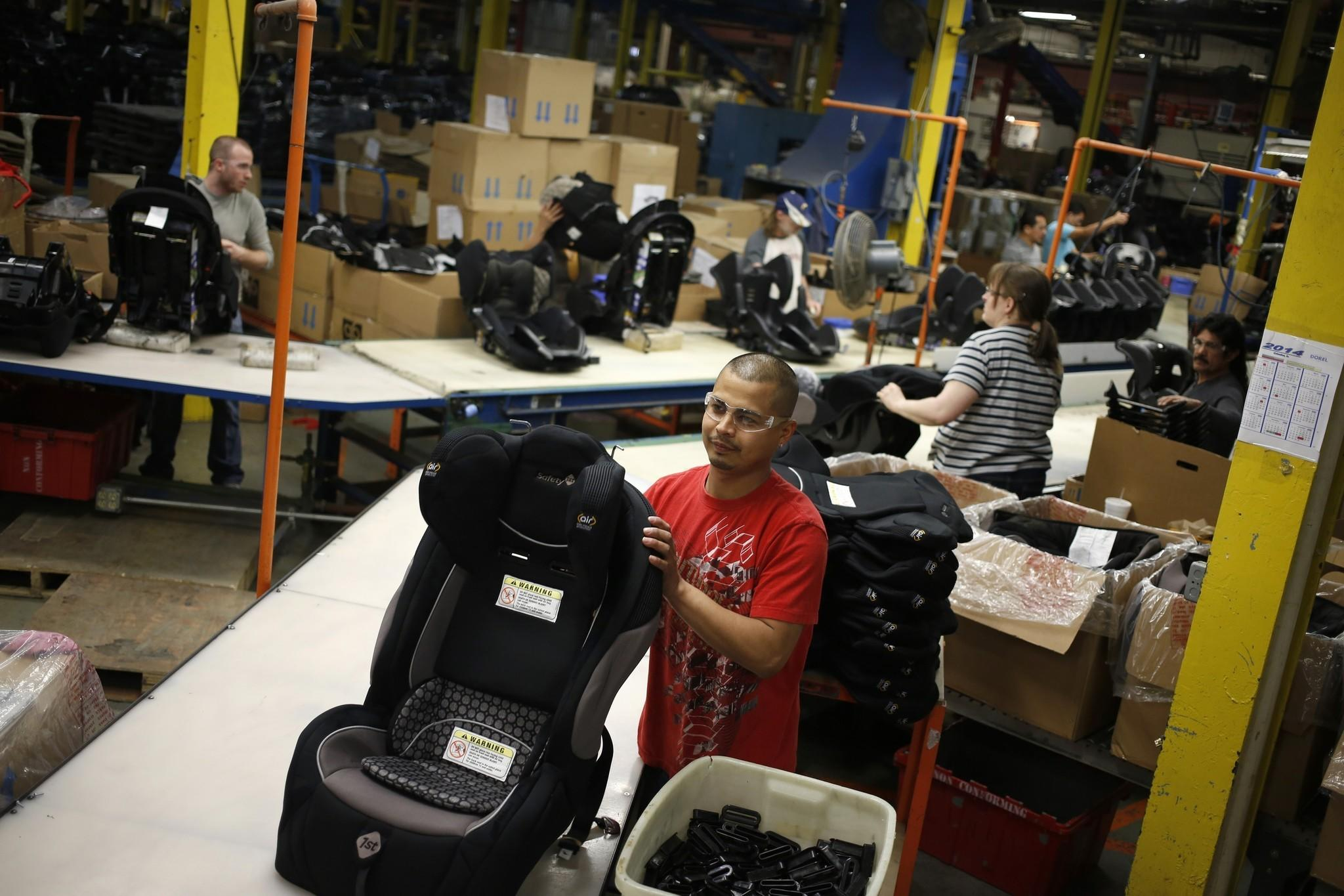 Noe Castaneda assembles child car seats at the Dorel Juvenile Group factory in Columbus, Ind.