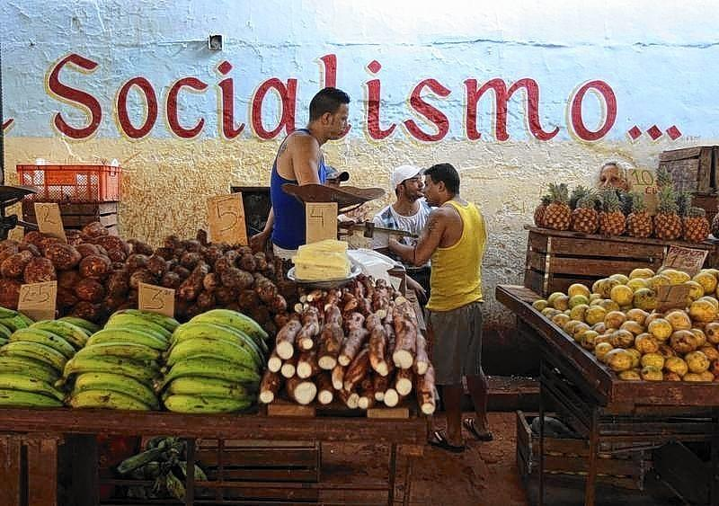 Vendors wait for customers at their stalls, with prices tagged in Cuban pesos, at a market in Havana in 2013.