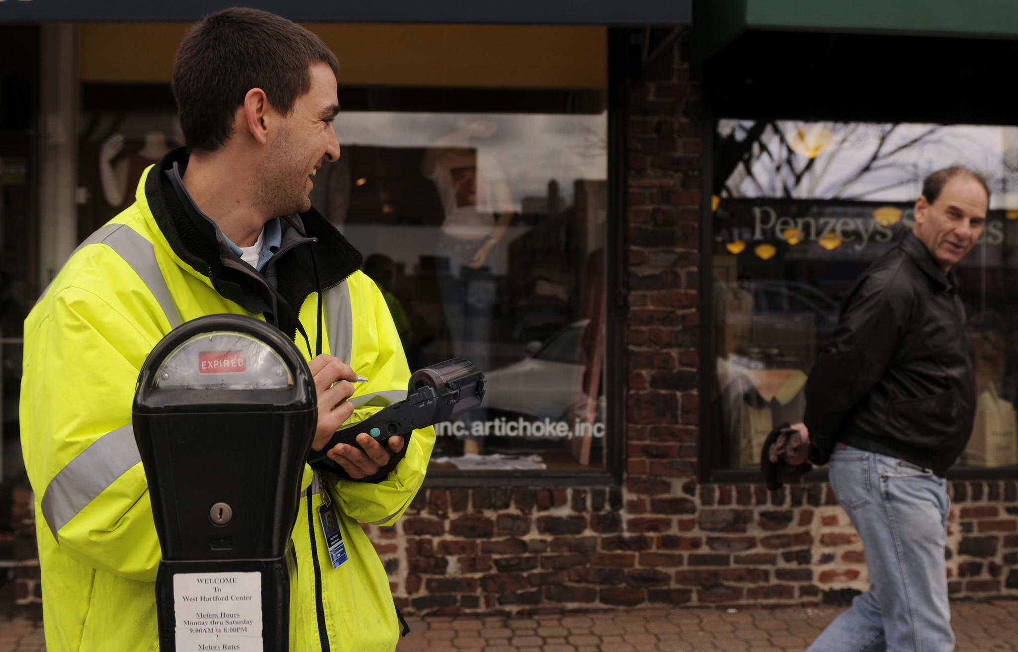West Hartford parking monitor Greg Michaud (at left) responds to a passerby on LaSalle Road while writing out a parking ticket in 2011.
