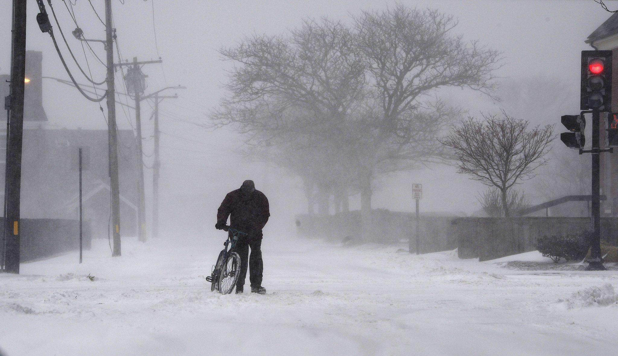 A cyclist walks his bicycle in white-out conditions in Hyannis, Mass., on Wednesday. A storm blanketed the area of Cape Cod, Mass., with up to six inches of snow and winds topping 60 mph, creating hazardous driving conditions and power outages.
