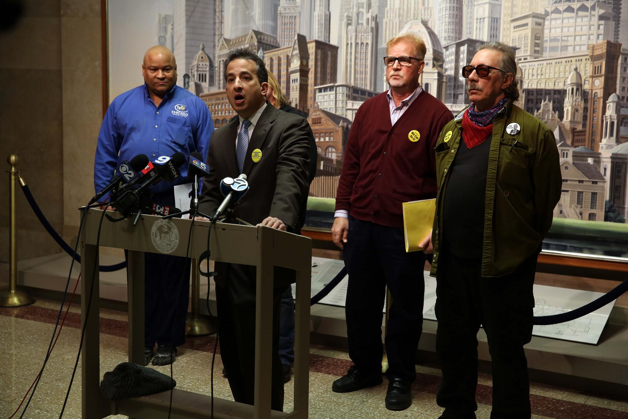 Attorney Jim Zouras, second from left, announces a lawsuit against Chicago's five major cab companies, alleging wage violations and misclassification of Chicago cab drivers as independent contractors.