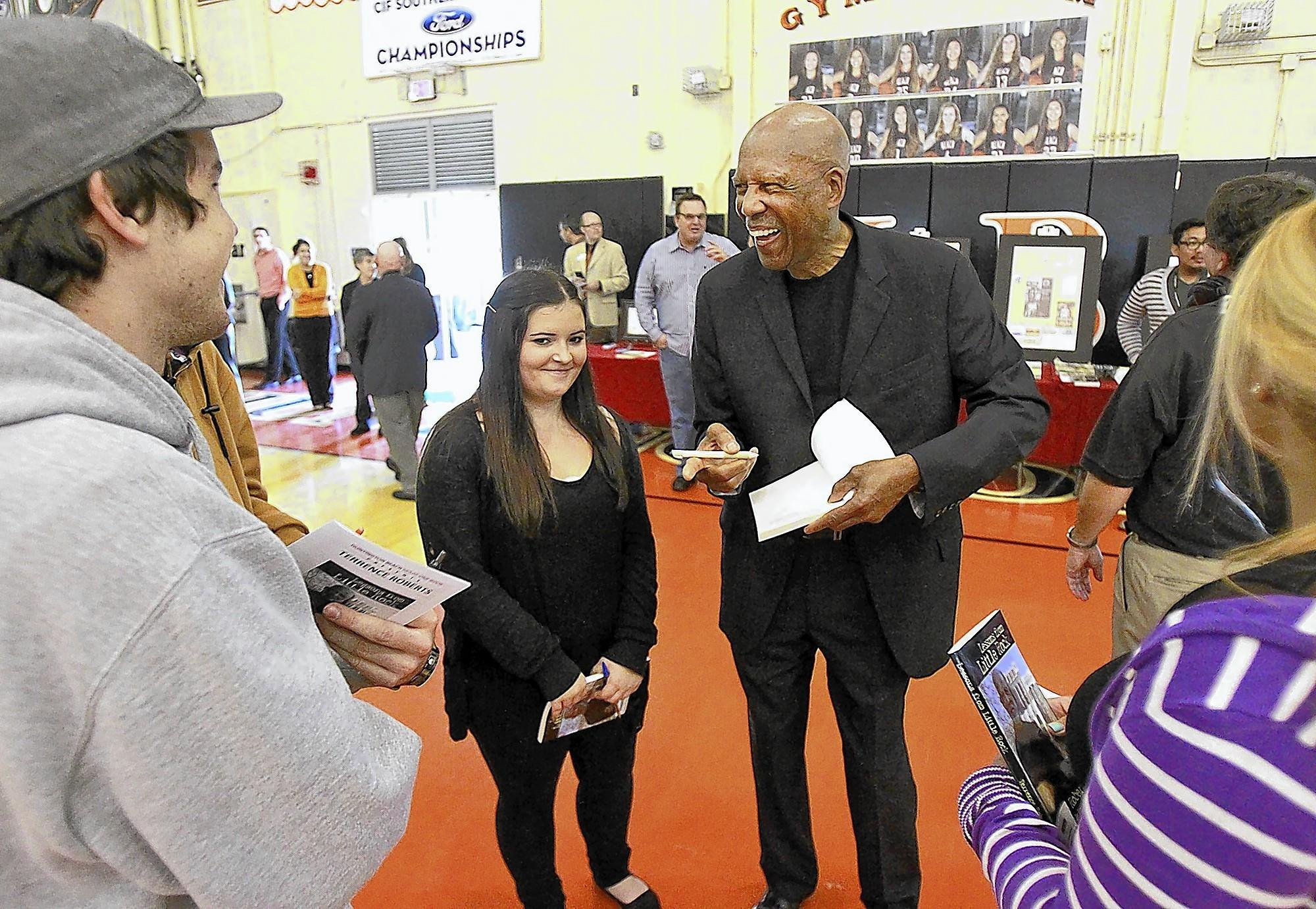 Terrence Roberts, one of the Little Rock Nine, signs autographs prior to his speaking engagement at the HB Reads assembly at Huntington Beach High School.