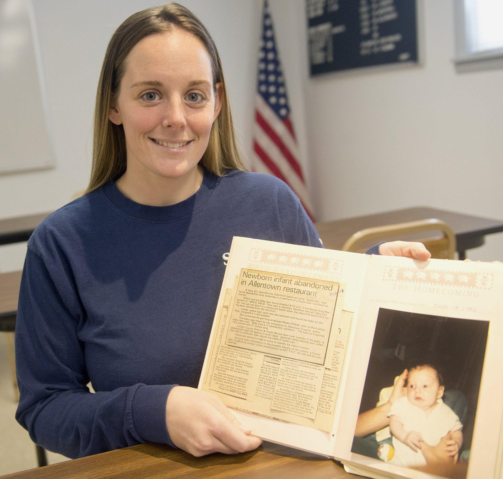 Katheryn Deprill, who was abandoned in an Allentown, Pa., Burger King, when she was about one hour old, is seeking her birth mother. Here, she poses for a photo with her baby book.