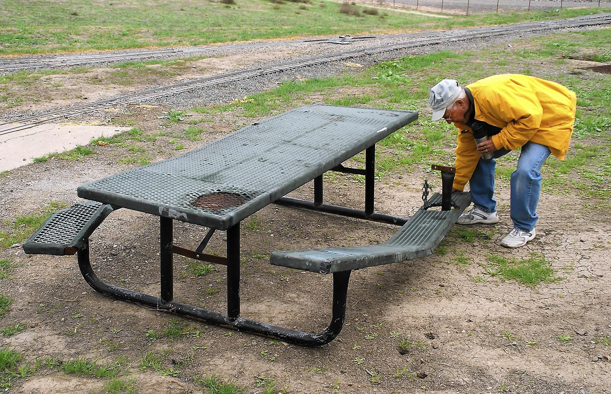 Orange County Model Engineers spokesman Hank Castignetti examines a broken table Wednesday in the club's Fairview Park train setup. Five other tables were vandalized there within the past few days.