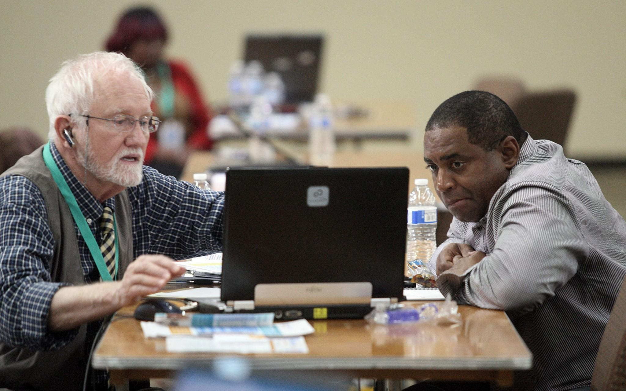 Mike Everding, left, a certified health insurance agent for Covered California, helps James Randle get a better health insurance rate at an Obamacare enrollment event at Faithful Central Bible Church in Inglewood.