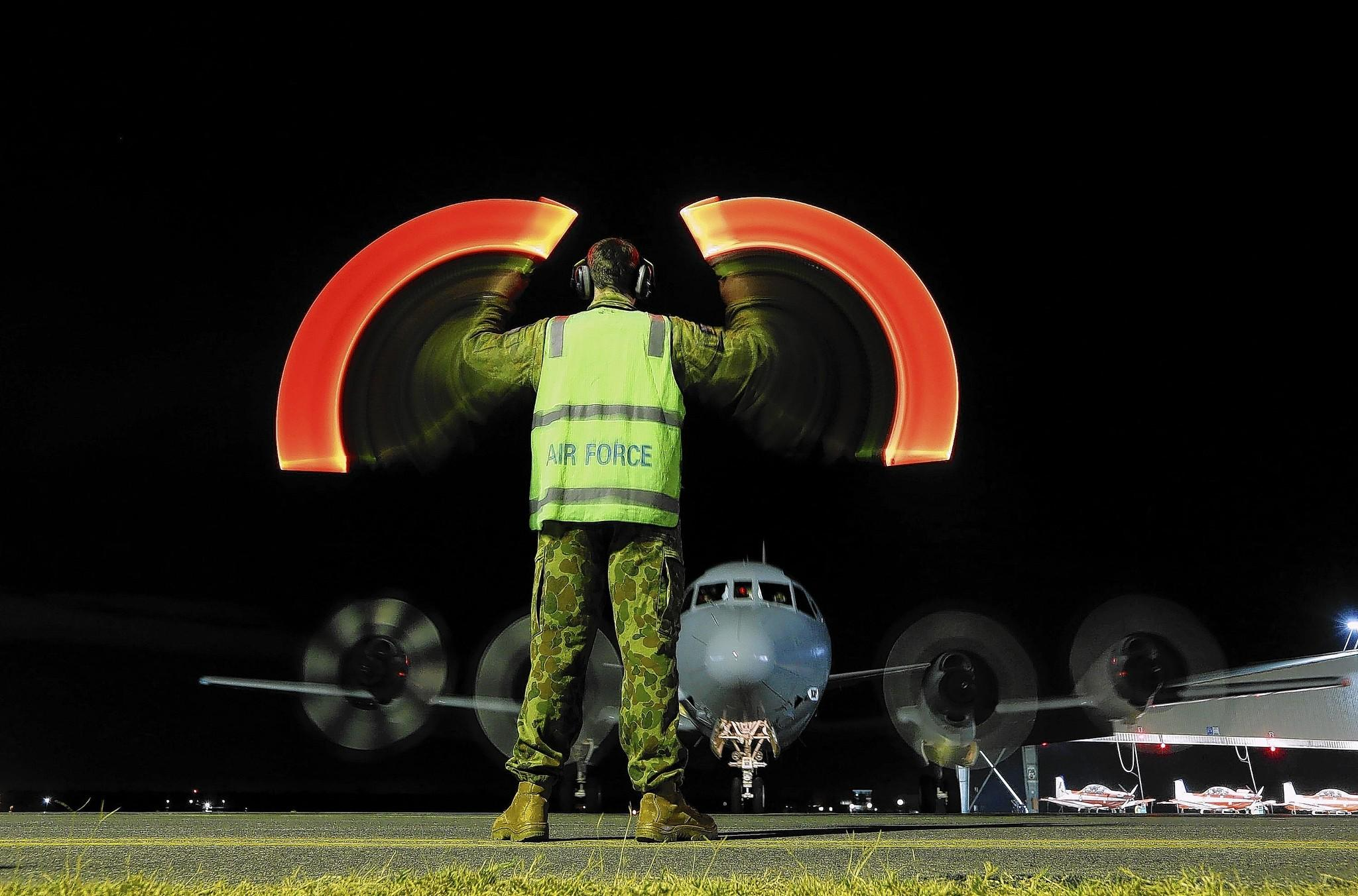 A ground crew member directs an Australian air force plane upon its return to the Pearce air base near Perth after it took part in a search for the Malaysia Airlines jetliner.