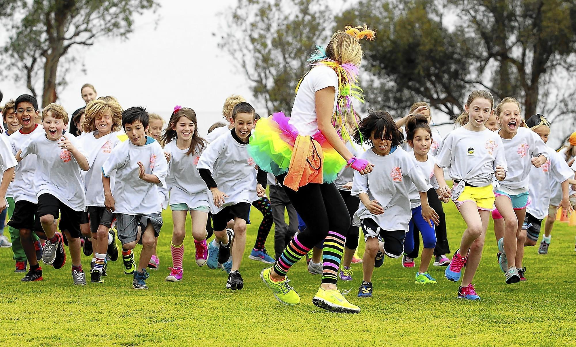 PTA volunteer Gorjana Reidel gets caught up in the start of the third-grade run as kids take off during the annual Top of the World jog-a-thon fundraiser on Friday.