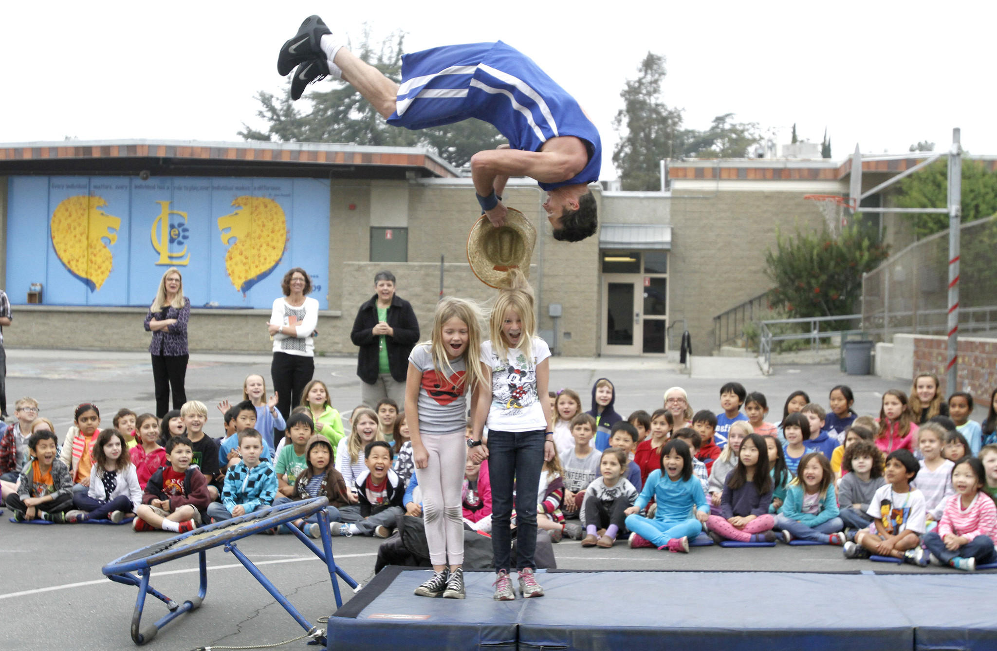 Keith Cousino of the TNT Dunk Squad flips as he grabs a hat off of student Katherine O'Callahghan during dunking demostration at La Canada Elementary School's playground in La Canada Flintridge on Tuesday, March 25, 2014. Grace Frame at center left also had her hat removed by another dunker.