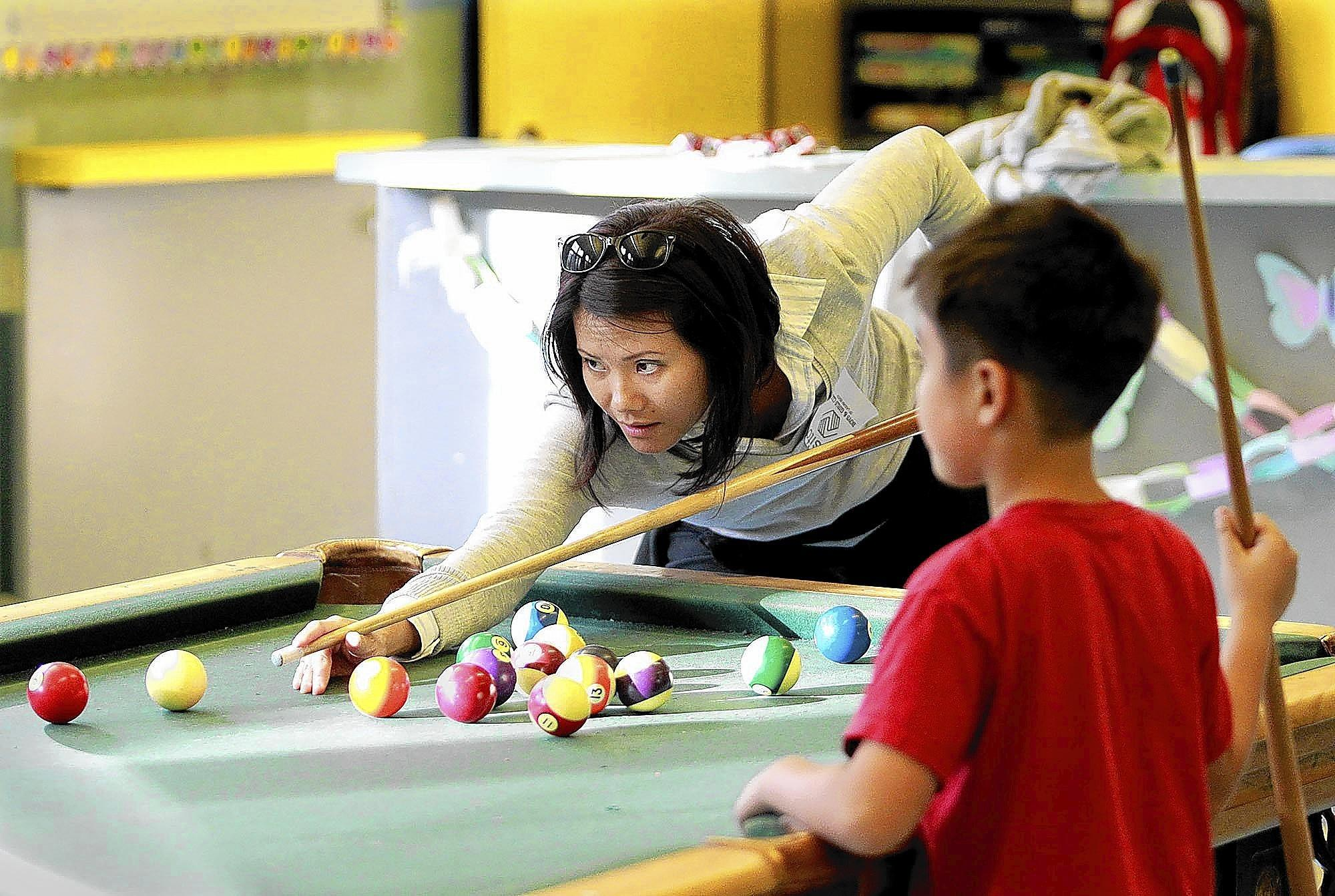 Loan Ulrich lines up a shot as her son Jacob, 9, looks on while enjoying a game of pool during the first open house at the Laguna Beach Boys & Girls Club on Wednesday night.