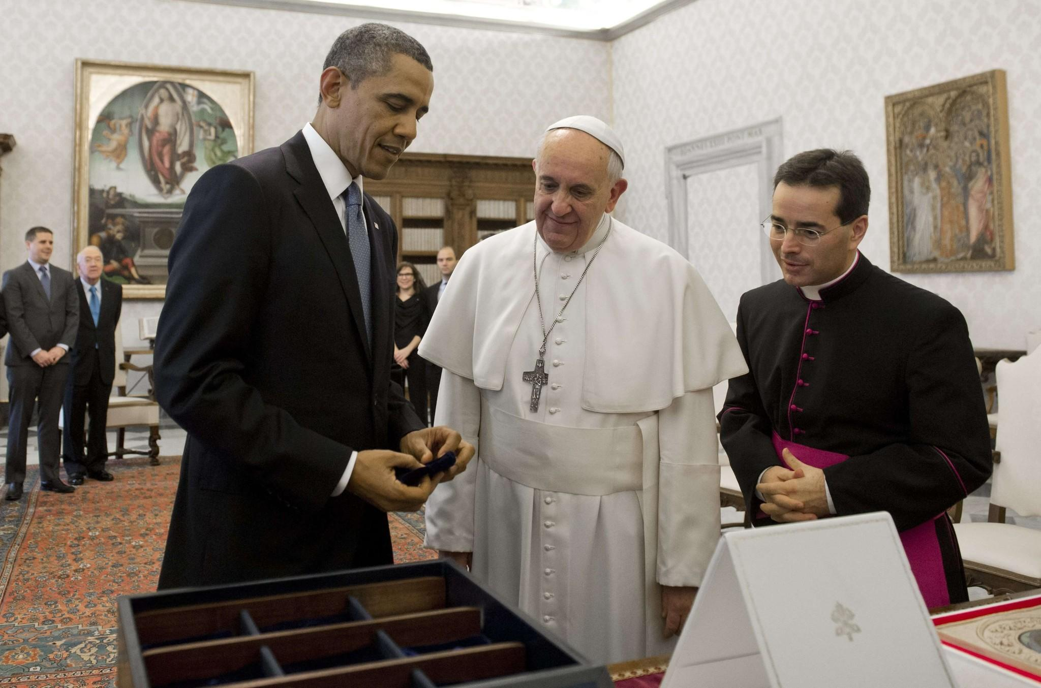 President Barack Obama presents Pope Francis with a custom-made seed chest featuring a variety of fruit and vegetable seeds from the White House garden during a private audience on March 27, 2014 at the Vatican. The chest was made of wood that came from the Baltimore Basilica.
