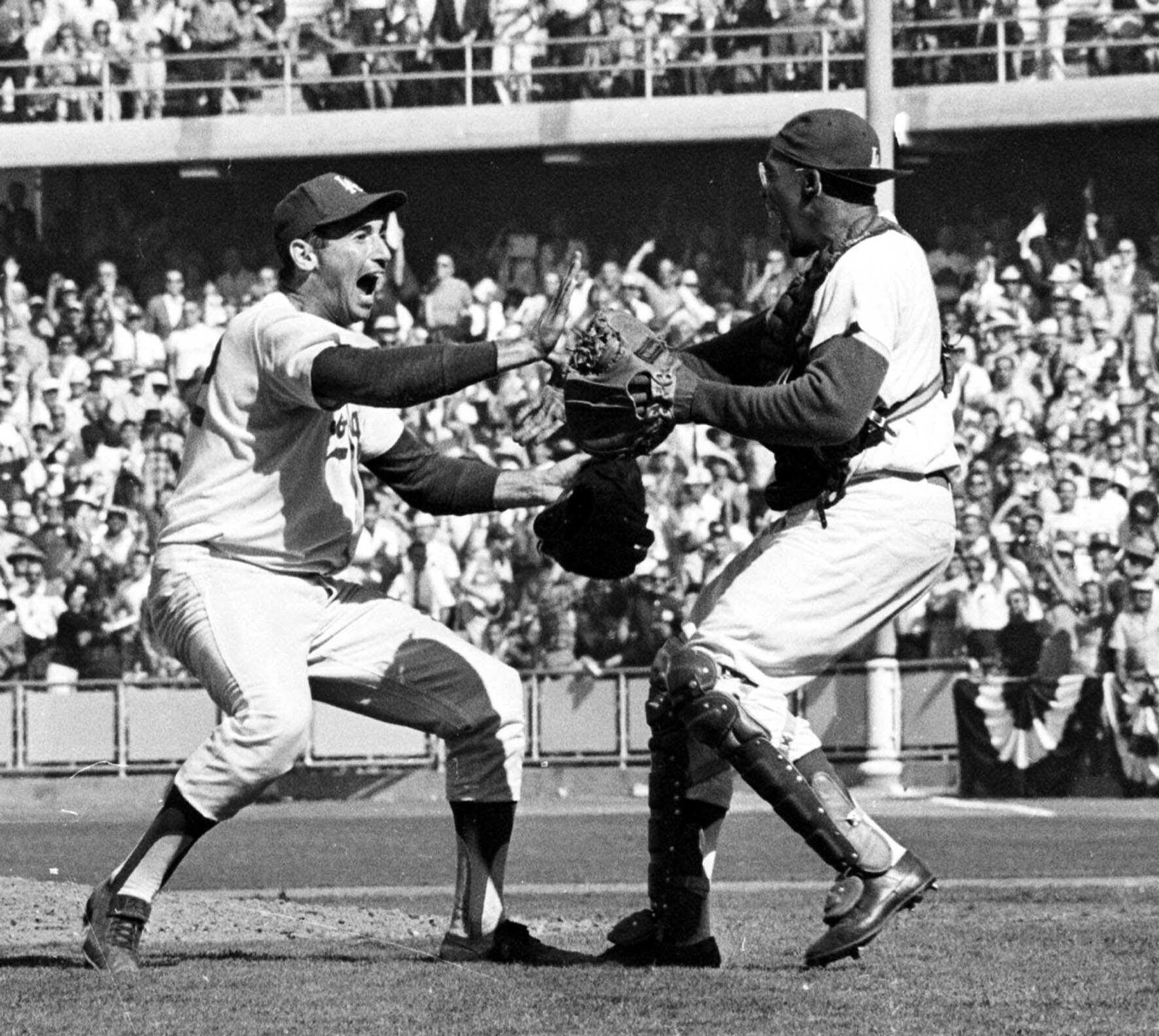 "Pitcher Sandy Koufax, left, and catcher John Roseboro celebrate after the Los Angeles Dodgers beat the New York Yankees, 2-1, to take the 1963 World Series in four games. ""Chasing Dreams,"" a new exhibit in a Philadelphia museum focuses on Koufax and other athletes who have faced discrimination and adversity."