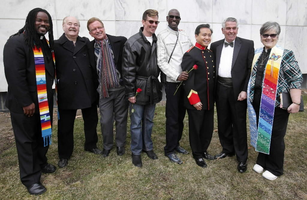 Reverend Roland Stringfellow (L) and Reverend Deb Dysert (R) pose for a group photo with three same-sex couples whose marriage they just jointly officiated outside the Oakland County Courthouse in Pontiac, Michigan on March 22.