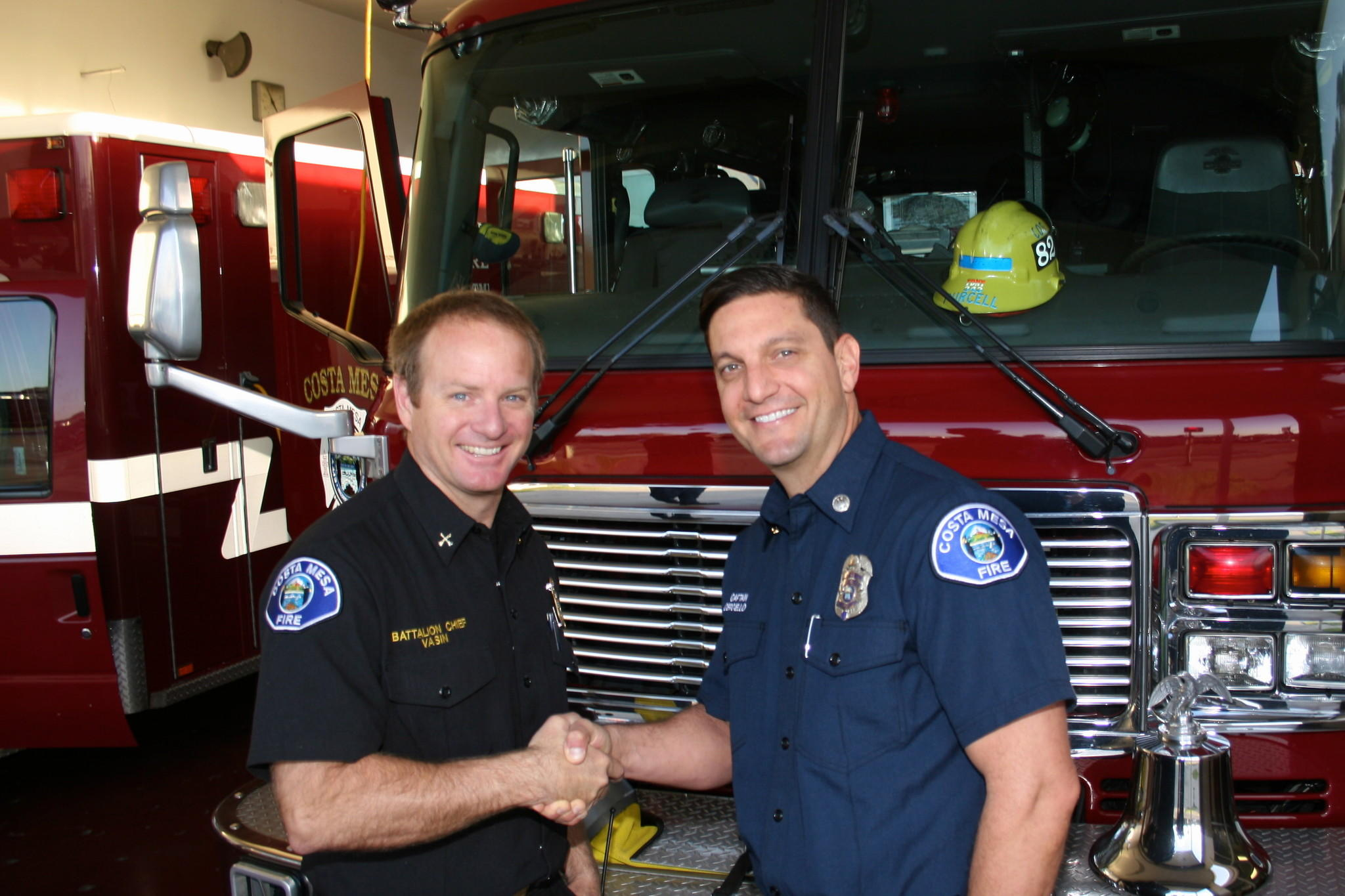 Battalion Chief Tim Vasin, left, congratulates Capt. Nick Cerciello on his first day of his new assignment.