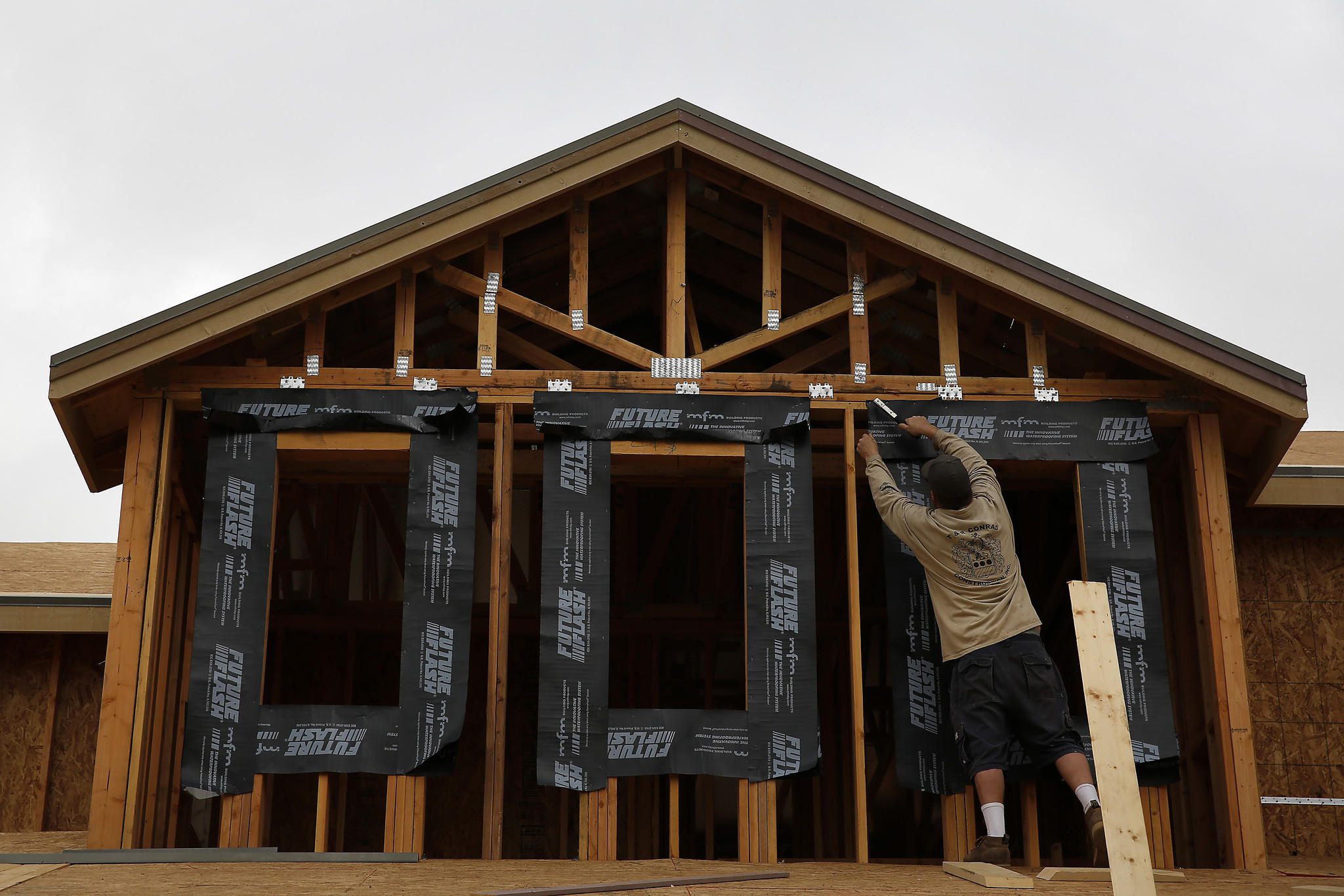 A contractor works on a home under construction in Irvine in January. California home sales fell last month.
