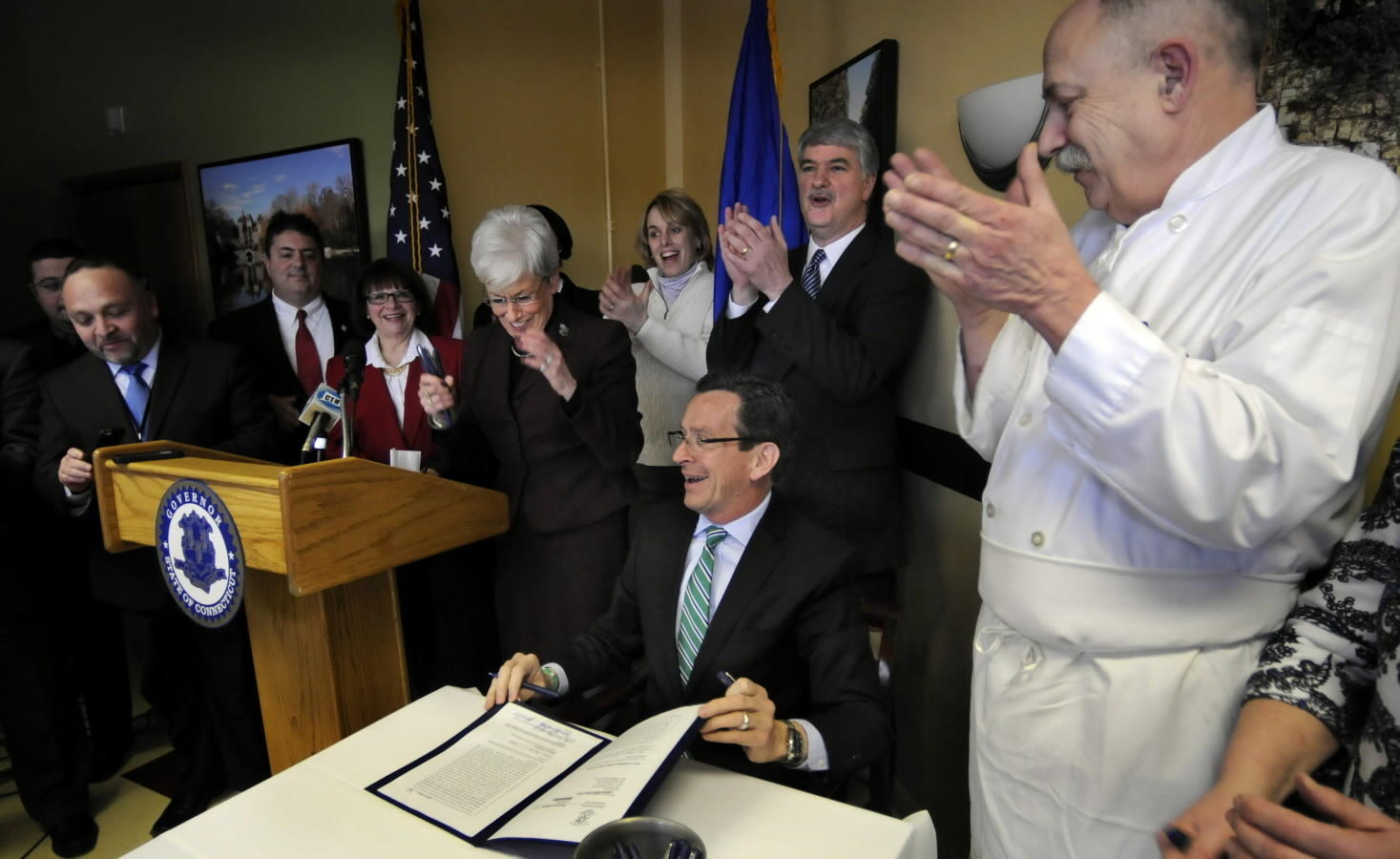 Gov. Dannel P. Malloy signs legislation increasing the state's minimum wage to $10.10 by 2017.