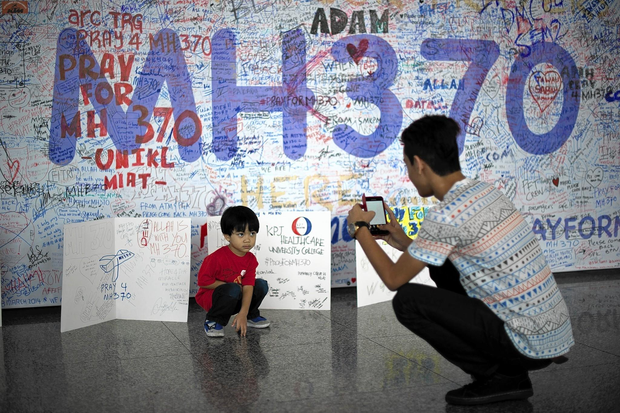 A visitor at Kuala Lumpur International Airport photographs messages for the passengers aboard the missing Malaysia Airlines flight.