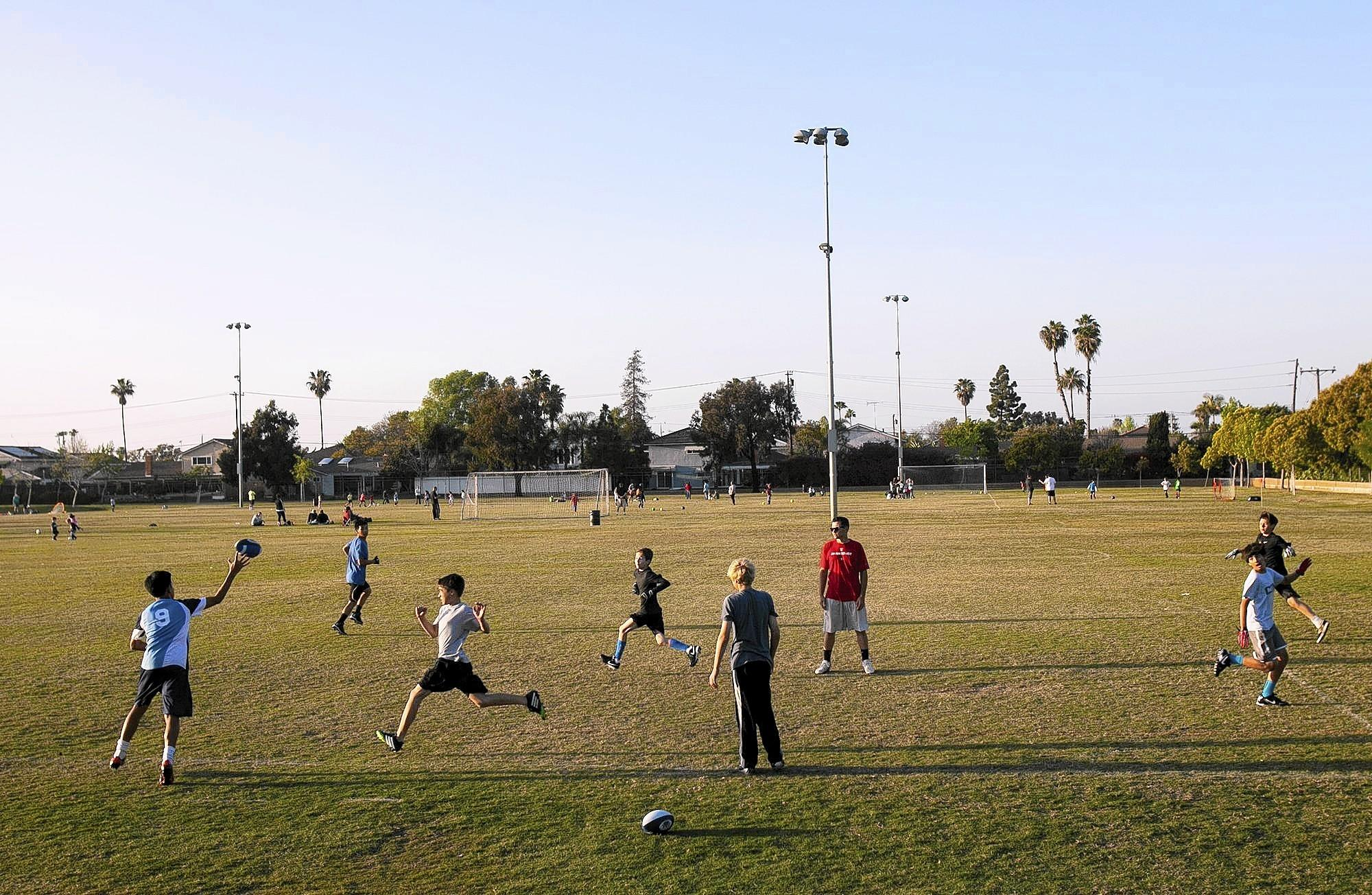 A group of boys with Newport-Mesa Friday Night Lights, a flag football program, practice on a recent afternoon at the Jack R. Hammett Sports Complex in Costa Mesa.