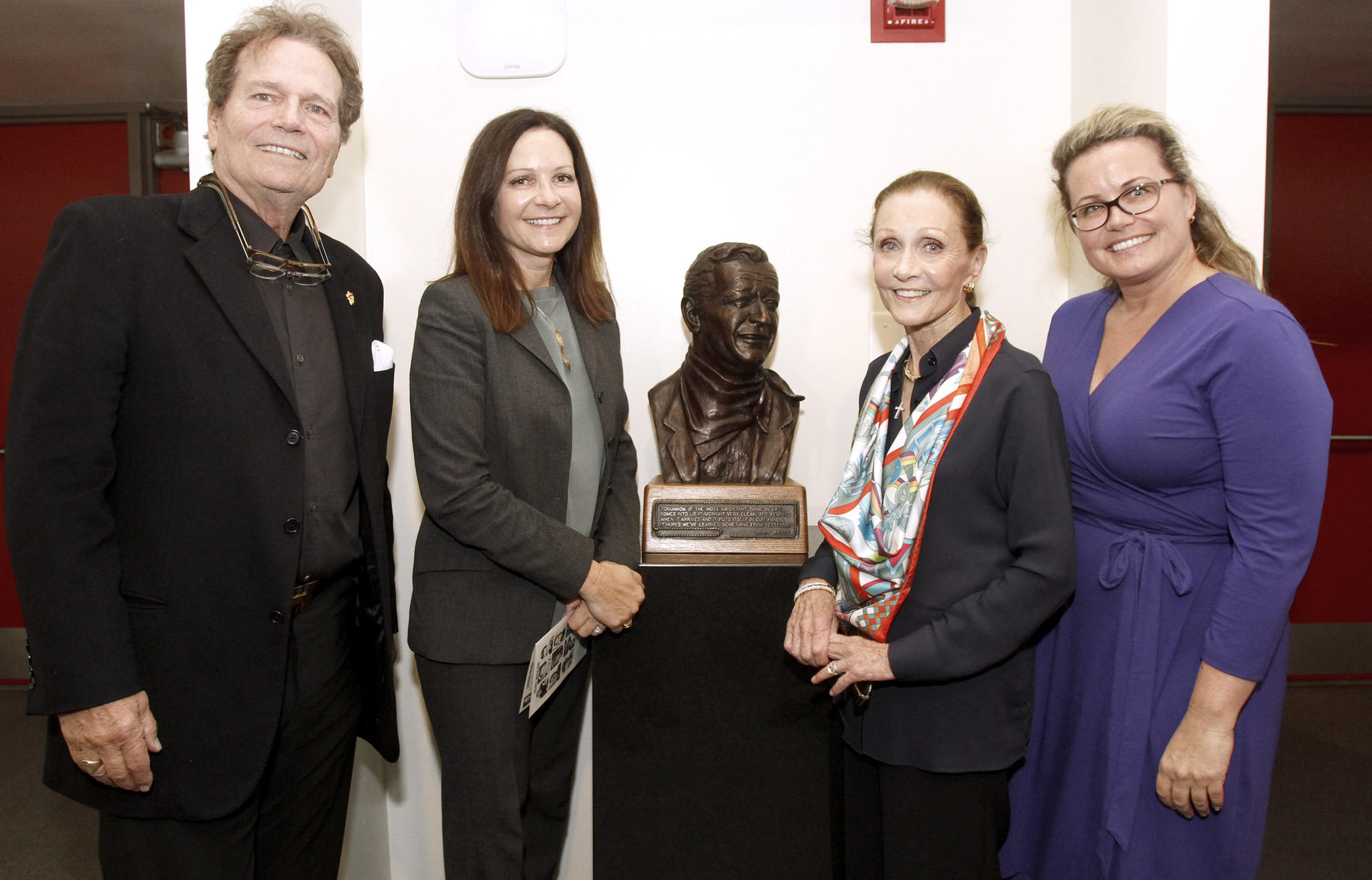 From left, John Wayne's son Patrick Wayne, John Wayne's granddaughter Maria King, King's mother and daughter-in-law (and widow to Michael Wayne) Gretchen Wayne, and granddaughter Josie Wayne attended the dedication ceremony for the Glendale High School John Wayne Performing Arts Center in Glendale on Friday, March 28, 2014.