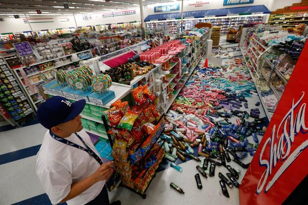 Cesar Zamora, night manager at the 99 Cent Only store on Imperial Highway, looks over aisles of fallen goods.