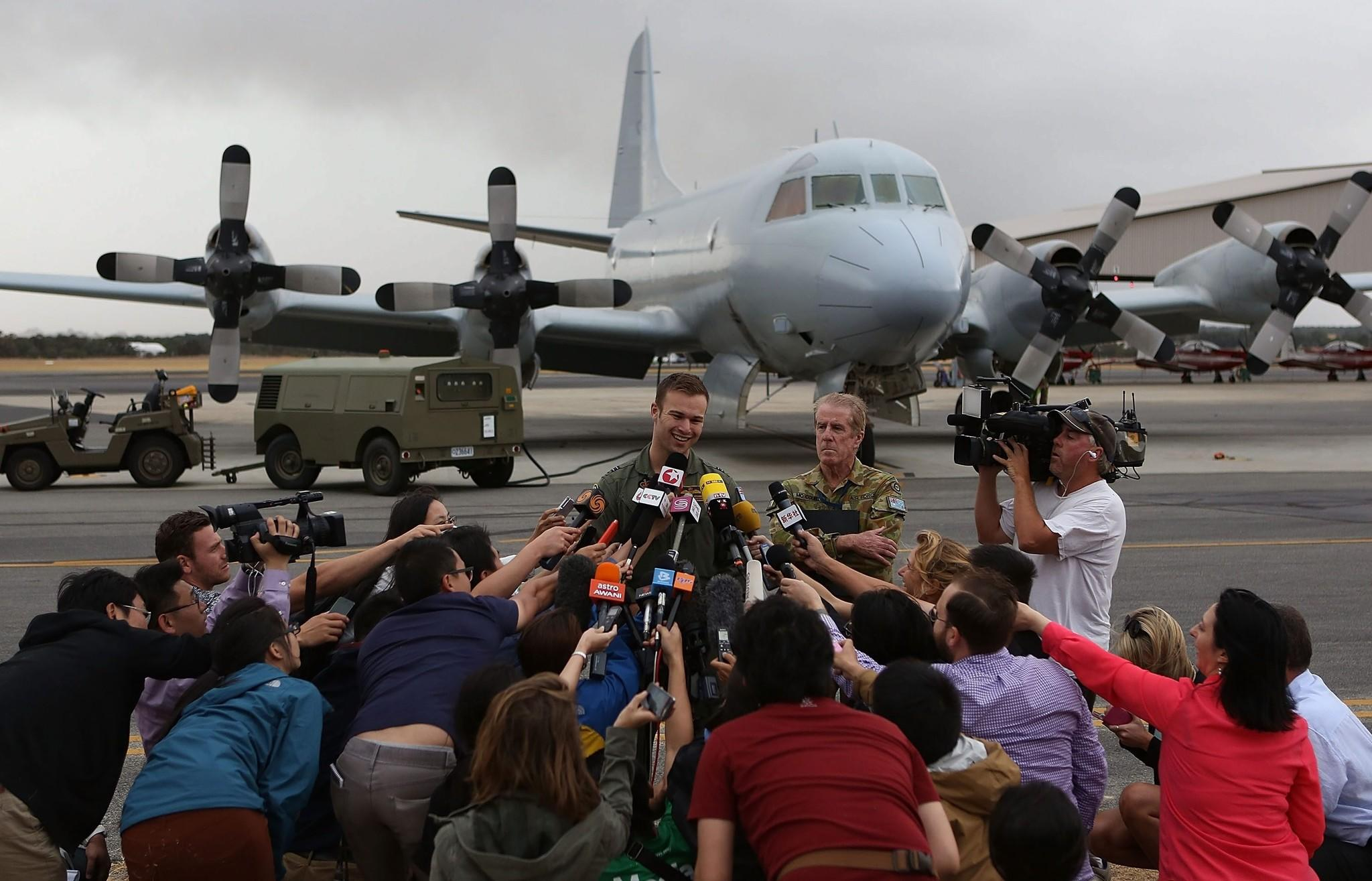 Flight Lt. Russell Adams of the Australian air force speaks to reporters in Perth after his AP-3C Orion returned from searching for wreckage from the missing Malaysia Airlines Flight 370.