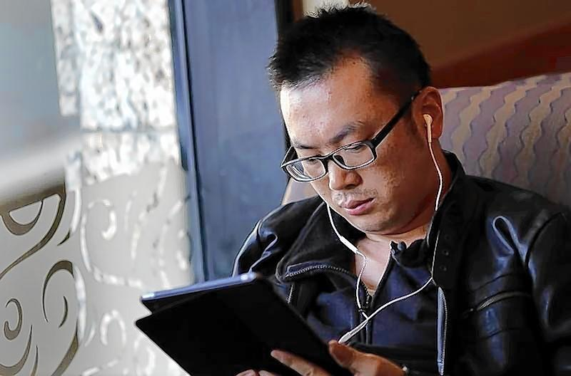 A man use his iPad inside a local coffee shop in downtown Shanghai, China.