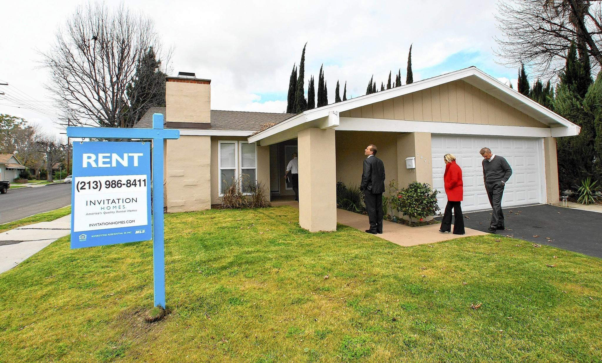 Officials from Blackstone Group's Invitation Homes tour a home in Canoga Park that the company bought, fixed up and turned into a rental property.