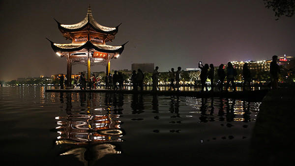 Chinese tourists stand in a pavilion lighted for an Earth Hour Day event at the West Lake in Hangzhou city, in China's Zhejiang province.