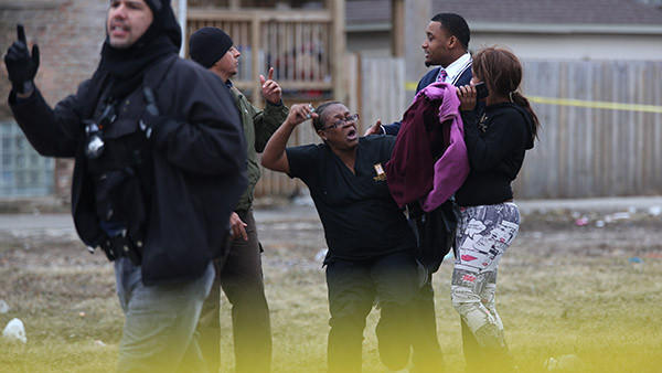 Sharon Shaw, center,  mother of victim, Raason Shaw, and one of her daughters breaks through the yellow tape and is confronted by police, after police-involved shooting in the 62nd block of S. Rhodes, early Saturday March 29, 2014.