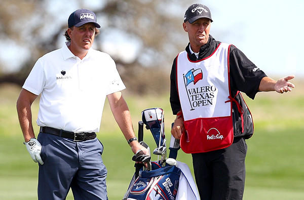 Phil Mickelson and caddie Jim Mackay discuss a shot during the third round of the Valero Texas Open at TPC San Antonio.