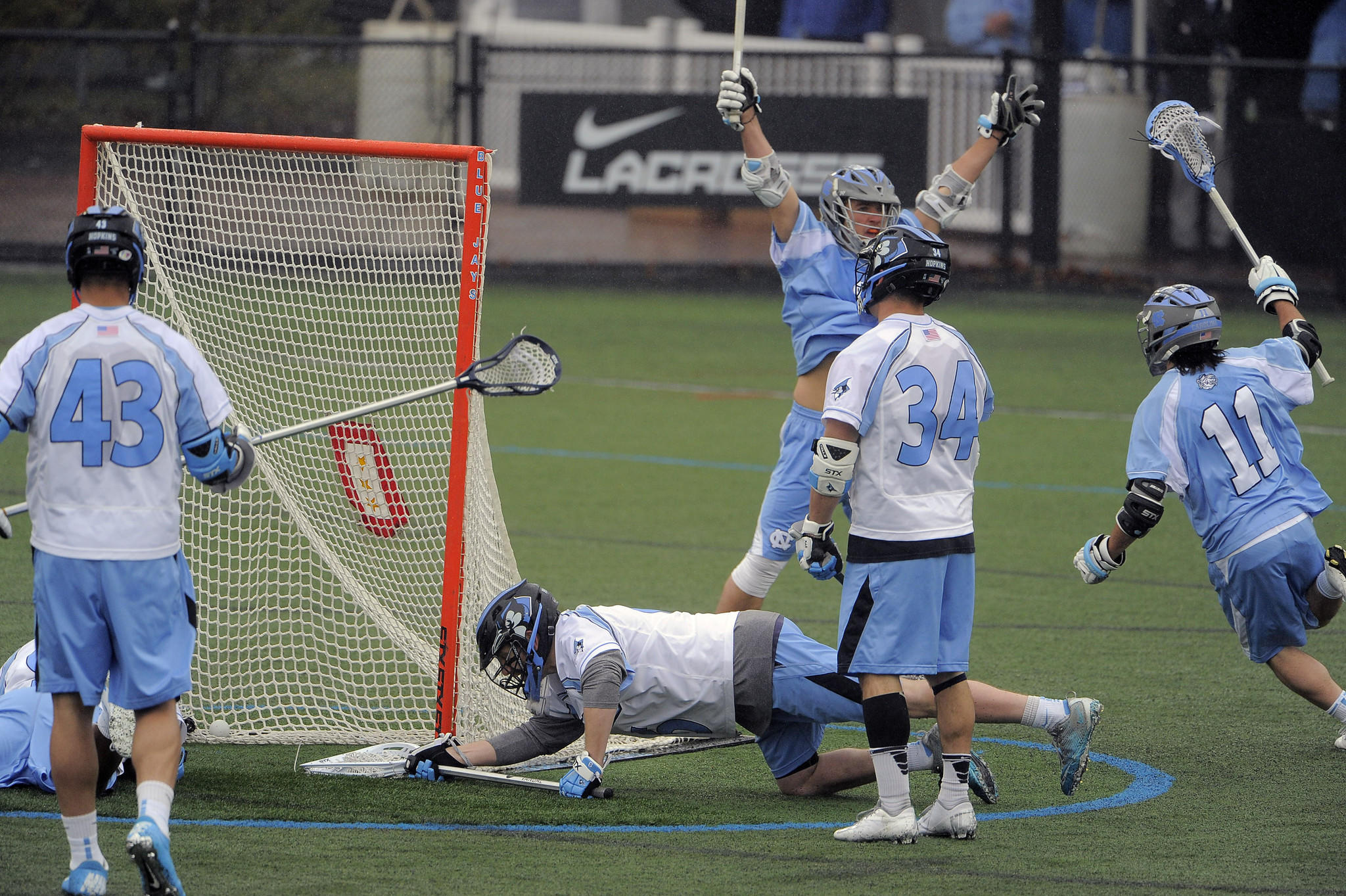 Johns Hopkins defender Jack Reilly (43) and long-stick midfielder Michael Pellegrino (34) watch goalie Eric Schneider (on ground) lunge at the ball, which rolls into the net as North Carolina attackman Joey Sankey (11) runs to celebrate his goal with attackman Jimmy Bitter.