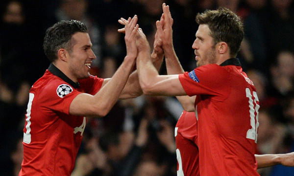 Manchester United's Robin van Persie, left, celebrates with teammate Michael Carrick after scoring against Olympiakos in a UEFA Champions League match on March 18. Stateside ownership of the Manchester United has done little to tarnish its legacy of success on the field.