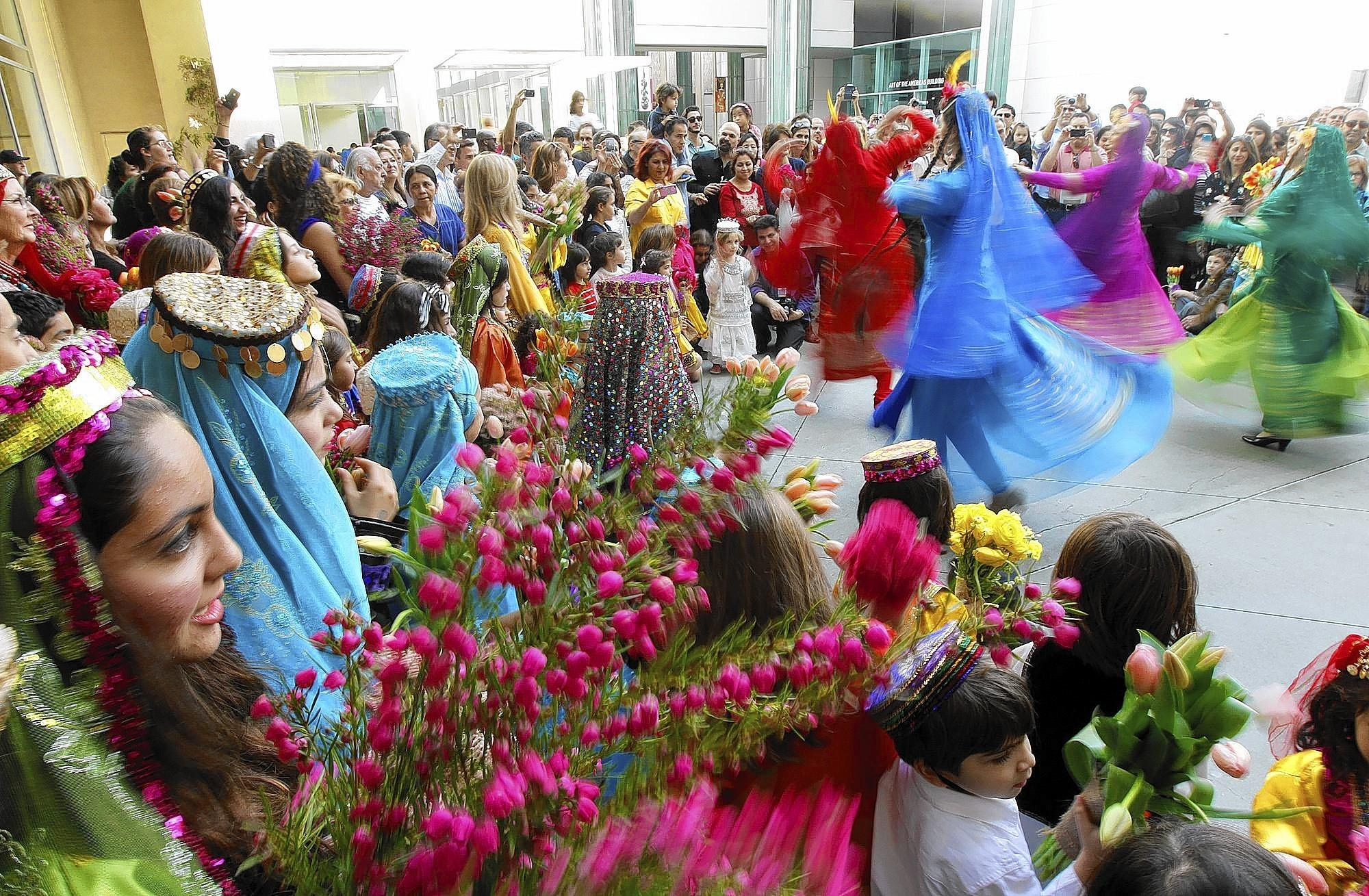 Dancers dressed in traditional Persian garments are surrounded by celebrants during an Iranian New Year celebration at the Los Angeles County Museum of Art.