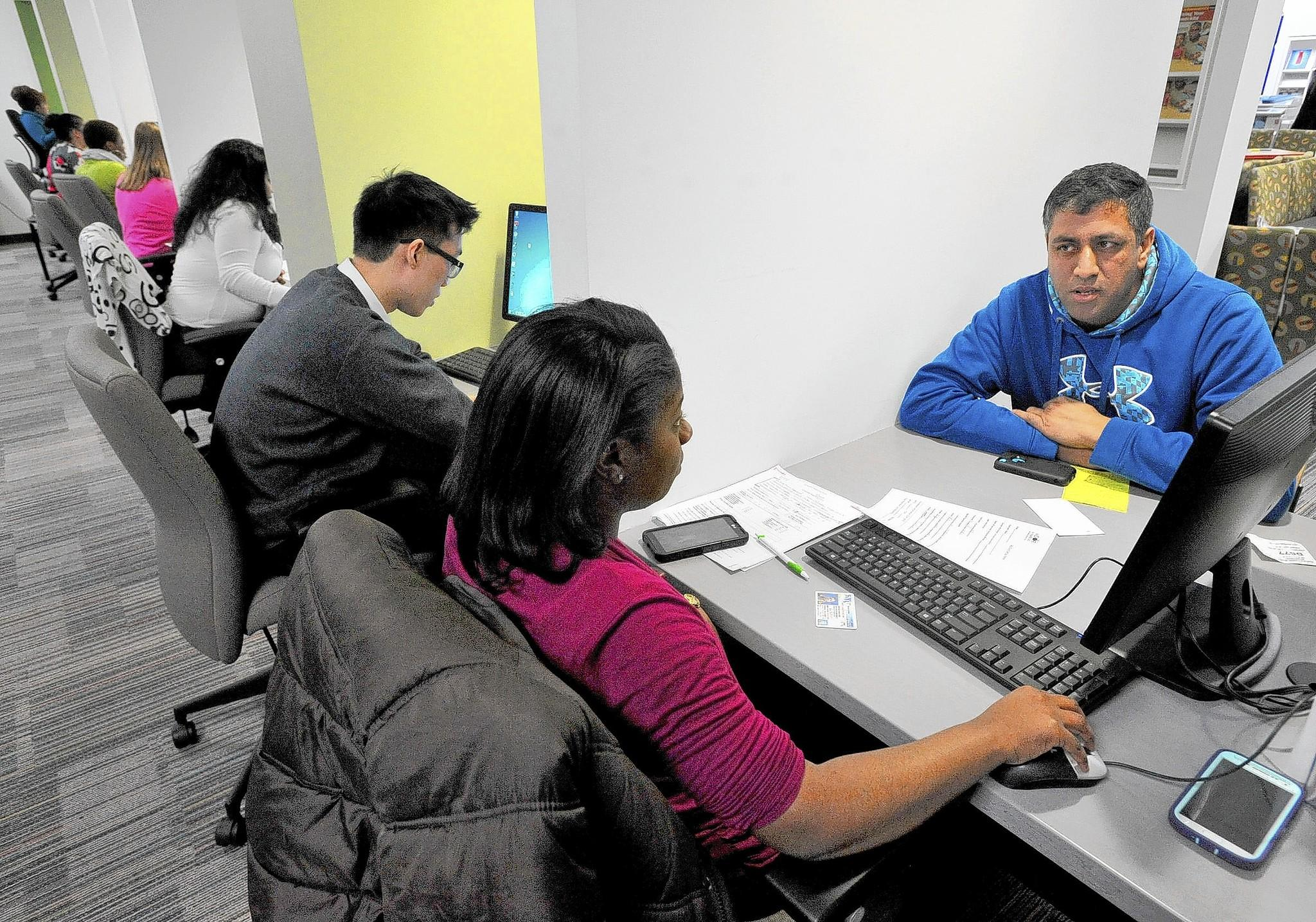 Raqueria Murvin, in front, assists consumer Rakesh Puri, 39, of Glenelg, right, apply for insurance.
