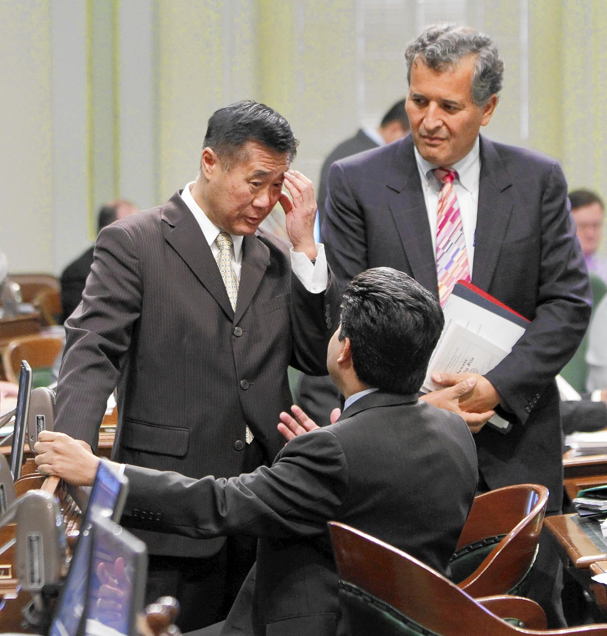 State Sen. LeLand Yee (D-San Francisco), left, talks with Assembly members in the Capitol in August 2012. Last week, Yee was arrested on charges of conspiring to illegally deal firearms, public corruption and wire fraud.