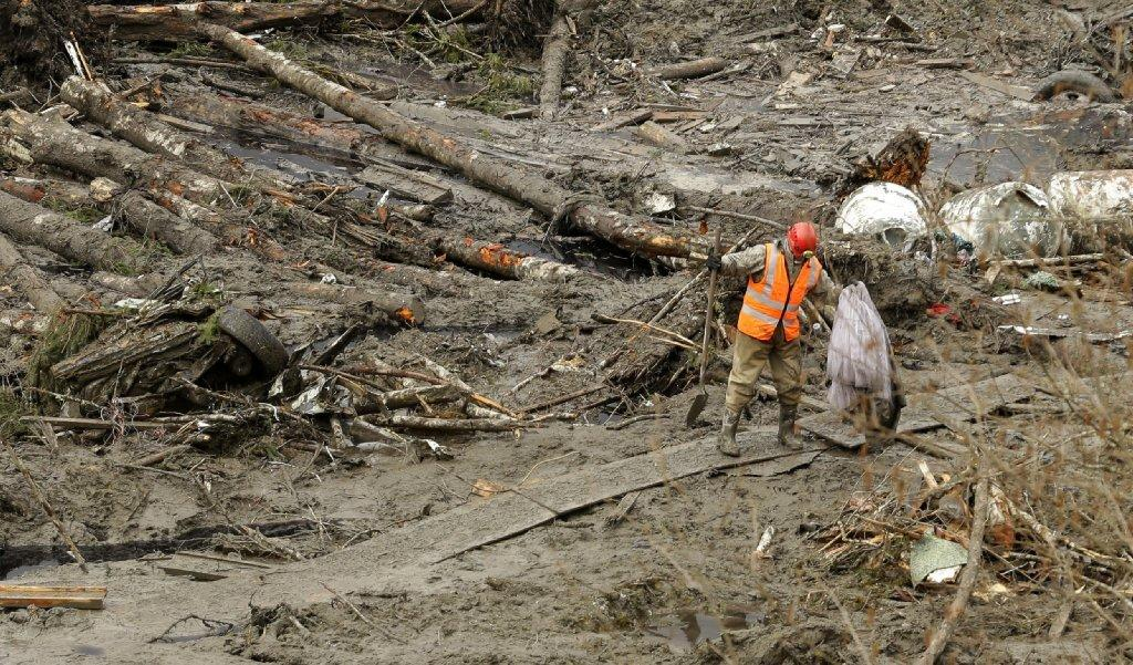 A worker navigates the muck left behind by a landslide in Snohomish County, Wash.
