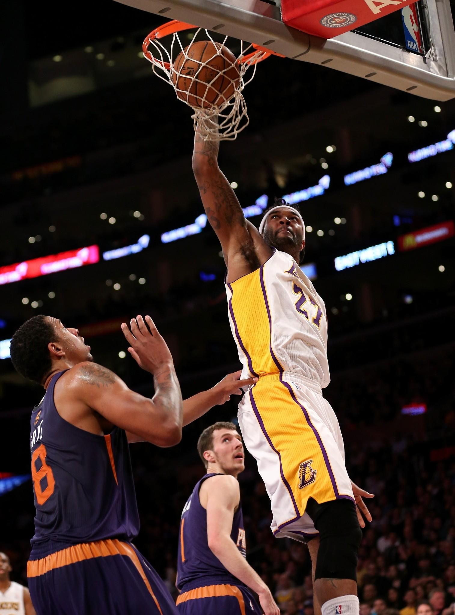 Lakers power forward Jordan Hill dunks over Phoenix Suns forward Channing Frye during the first half of their game at Staples Center.