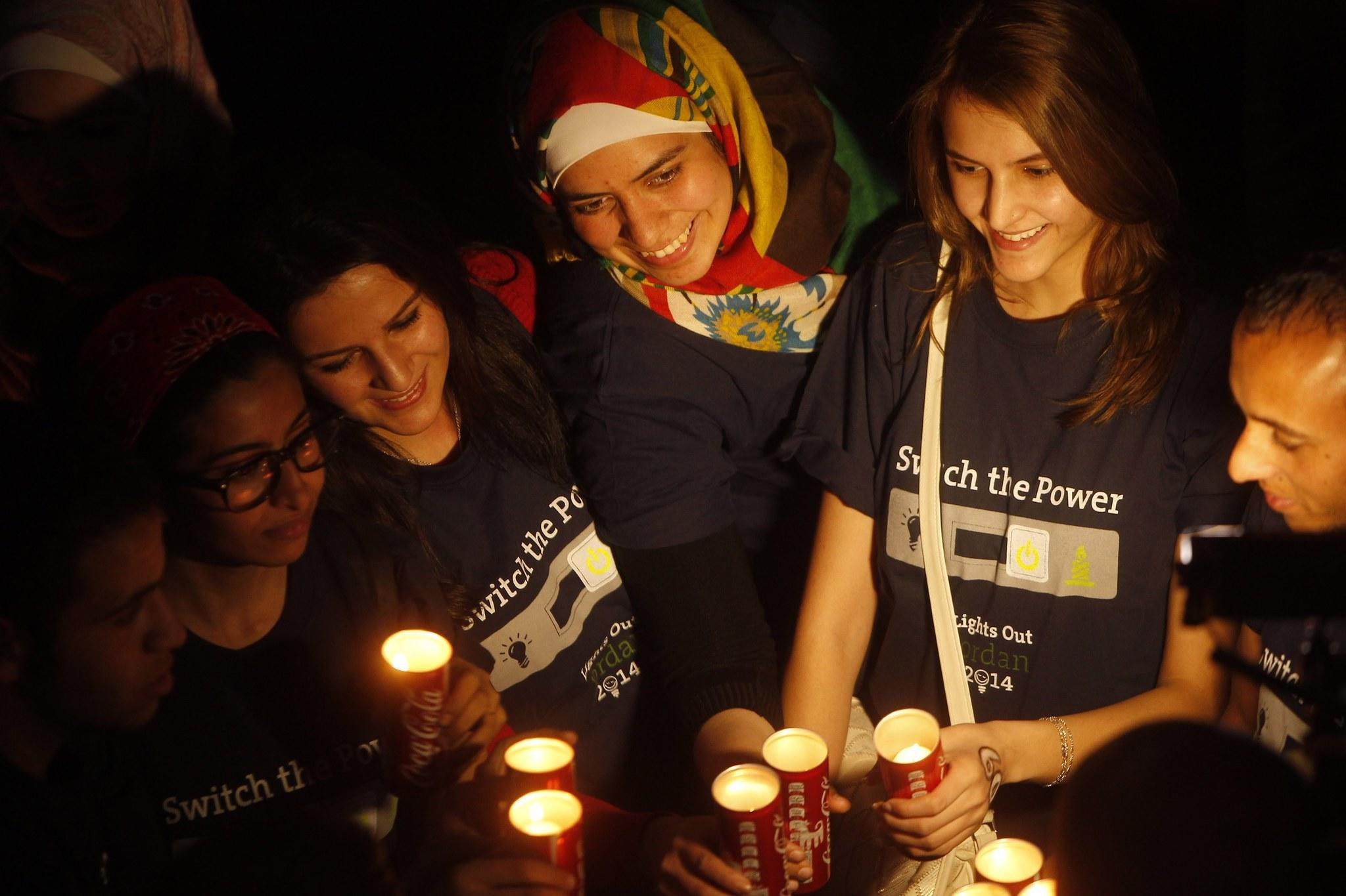 People hold candles during Earth Hour after the lights were turned off in central Amman on March 29.
