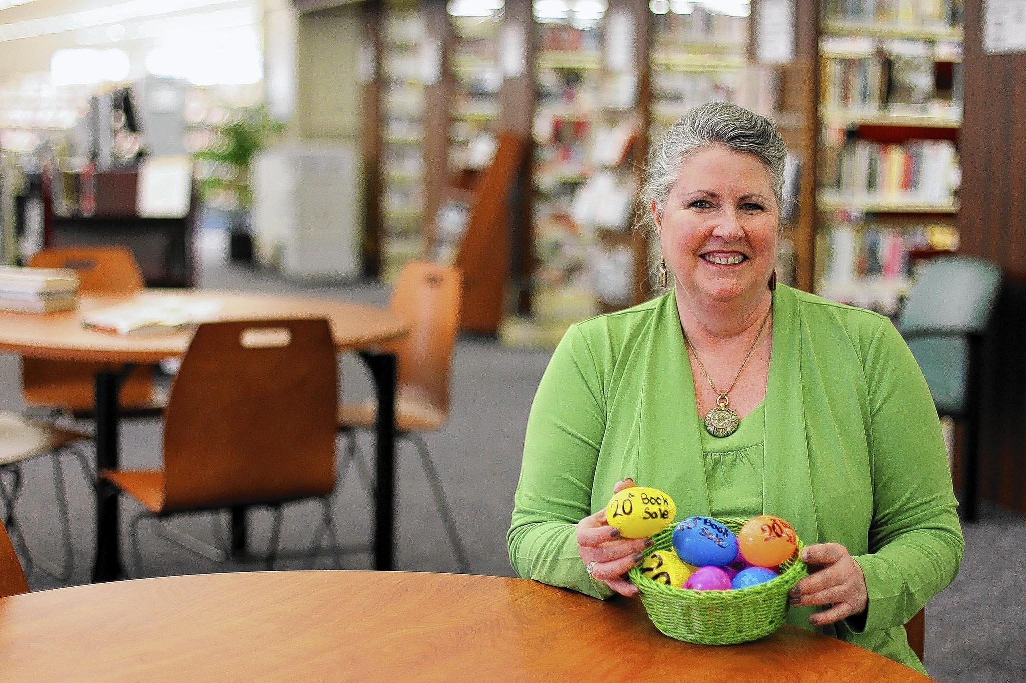 Friends of the Towson Library volunteer and coordinator of business memberships Judy Gregory poses for a photo with a basket of plastic eggs that will be hidden throughout the library and entitles the finder to a free bookduring the Friends of the Towson Library's annual used book sale from April 10-13.