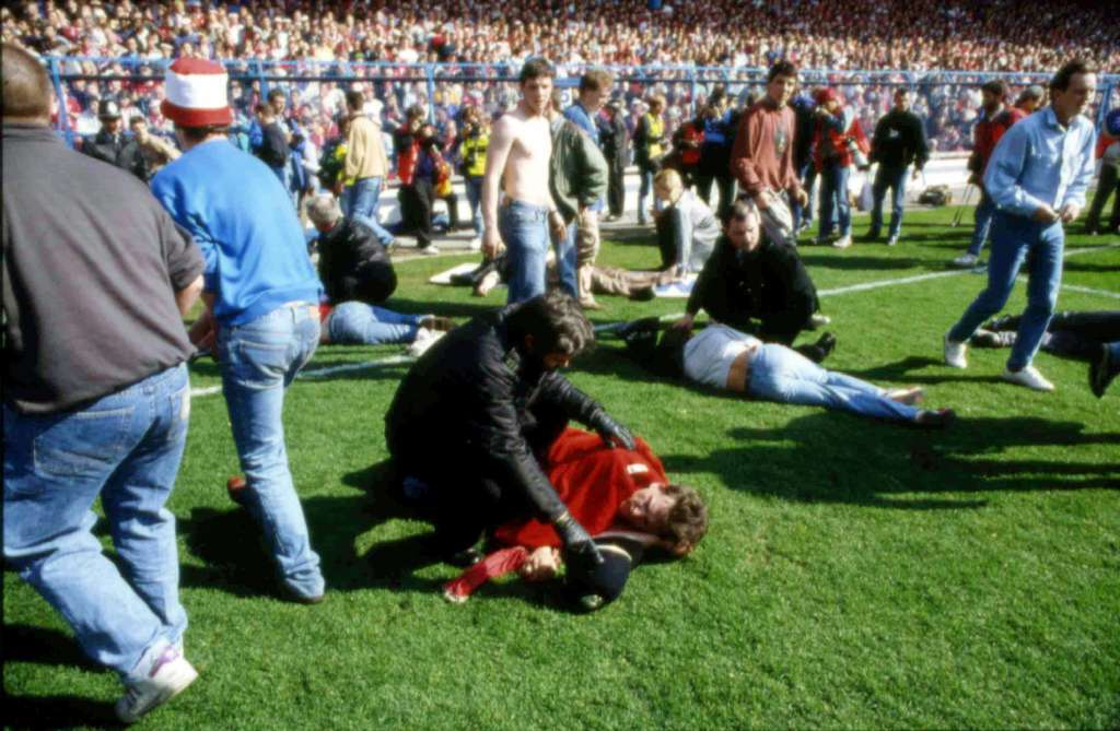 Police, stewards and others tend to injured soccer fans on the field at Hillsborough Stadium.