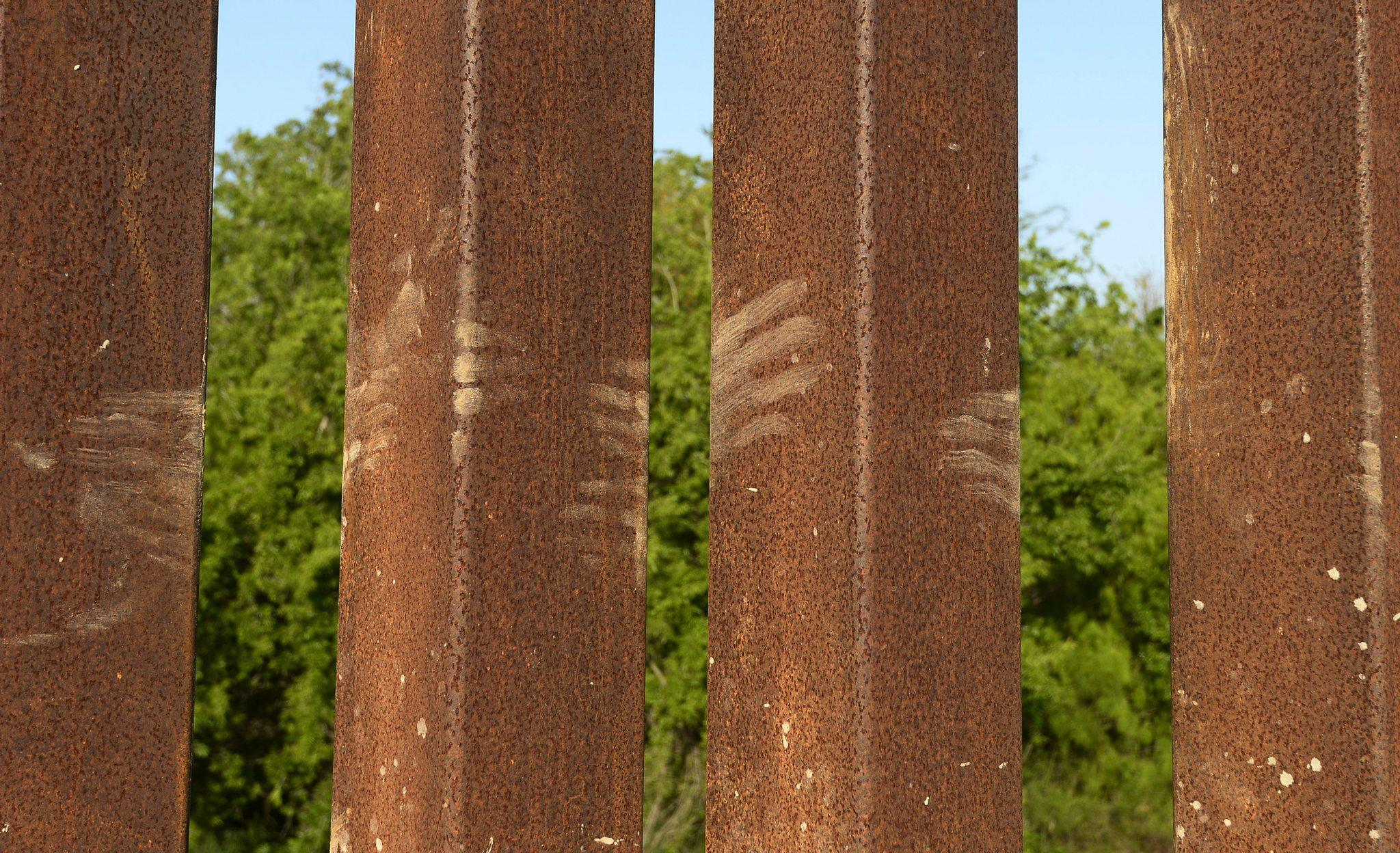 Muddy hand prints on the border fence left by people climbing over from Mexico along the Rio Grande near McAllen, Texas.