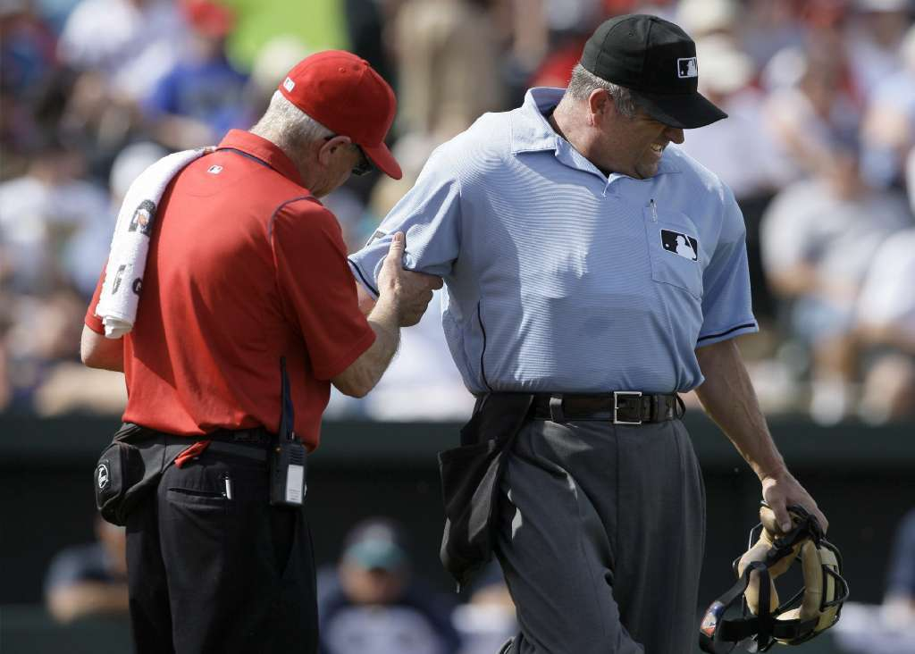 Umpire Dale Scott is checked by a trainer after being hit by a pitch.