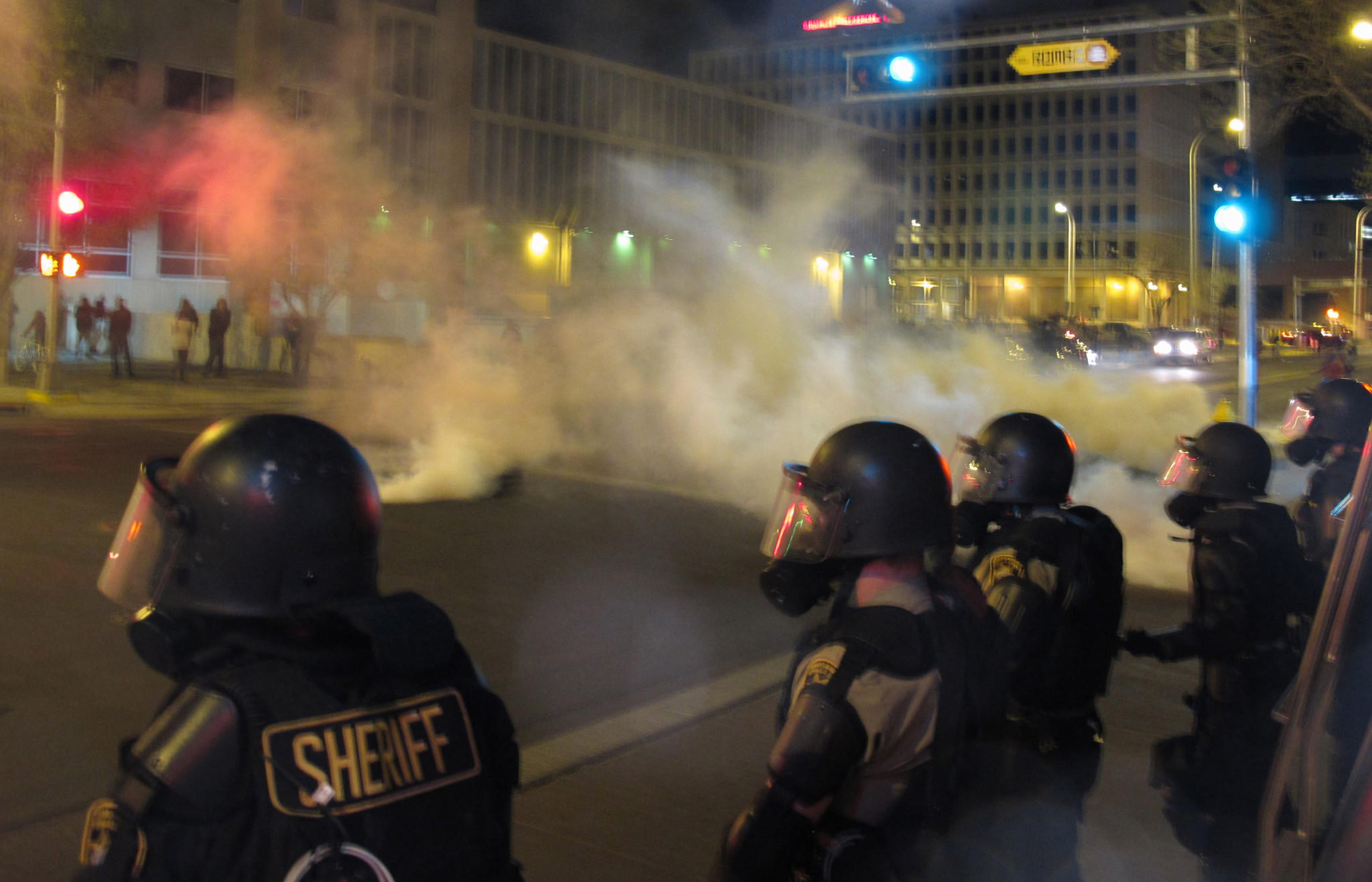 Riot police launch tear gas toward activists in downtown Albuquerque following a Sunday protest around the city over a series of deadly police shootings.