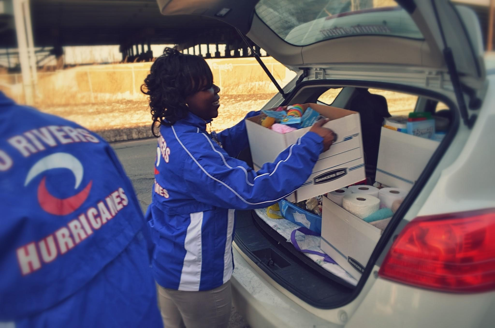 CREC Two Rivers student-athlete, Kassondra Ashley loads donations into a car to go to the CT Humane Society.